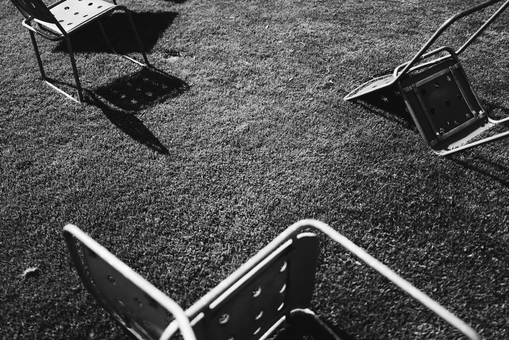 grayscale photo of gray chairs on grass field