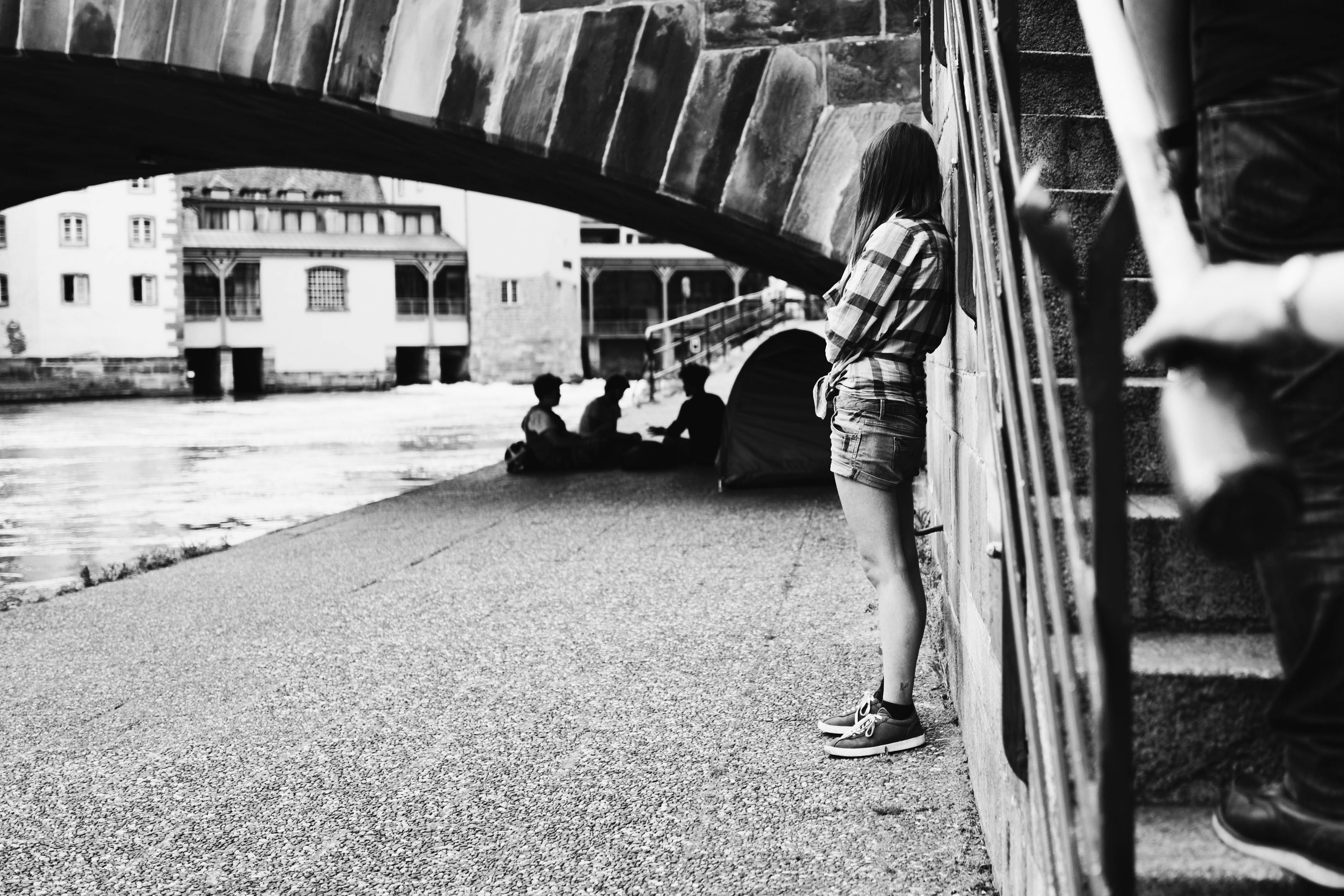 A black-and-white shot of a girl standing near a bridge and looking at people sitting under the bridge