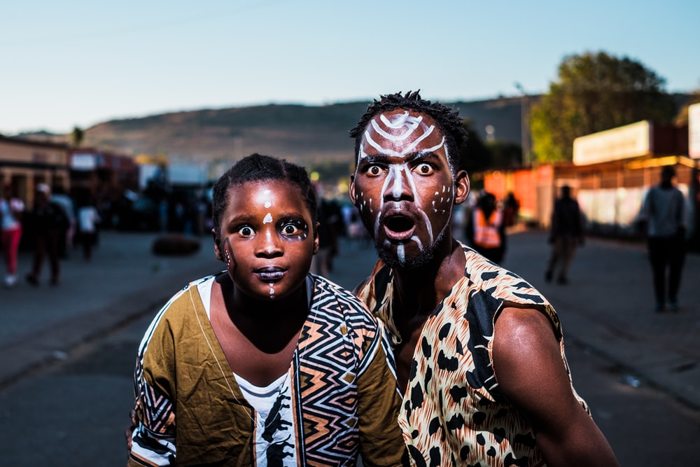 two people with face paints taking photo in street