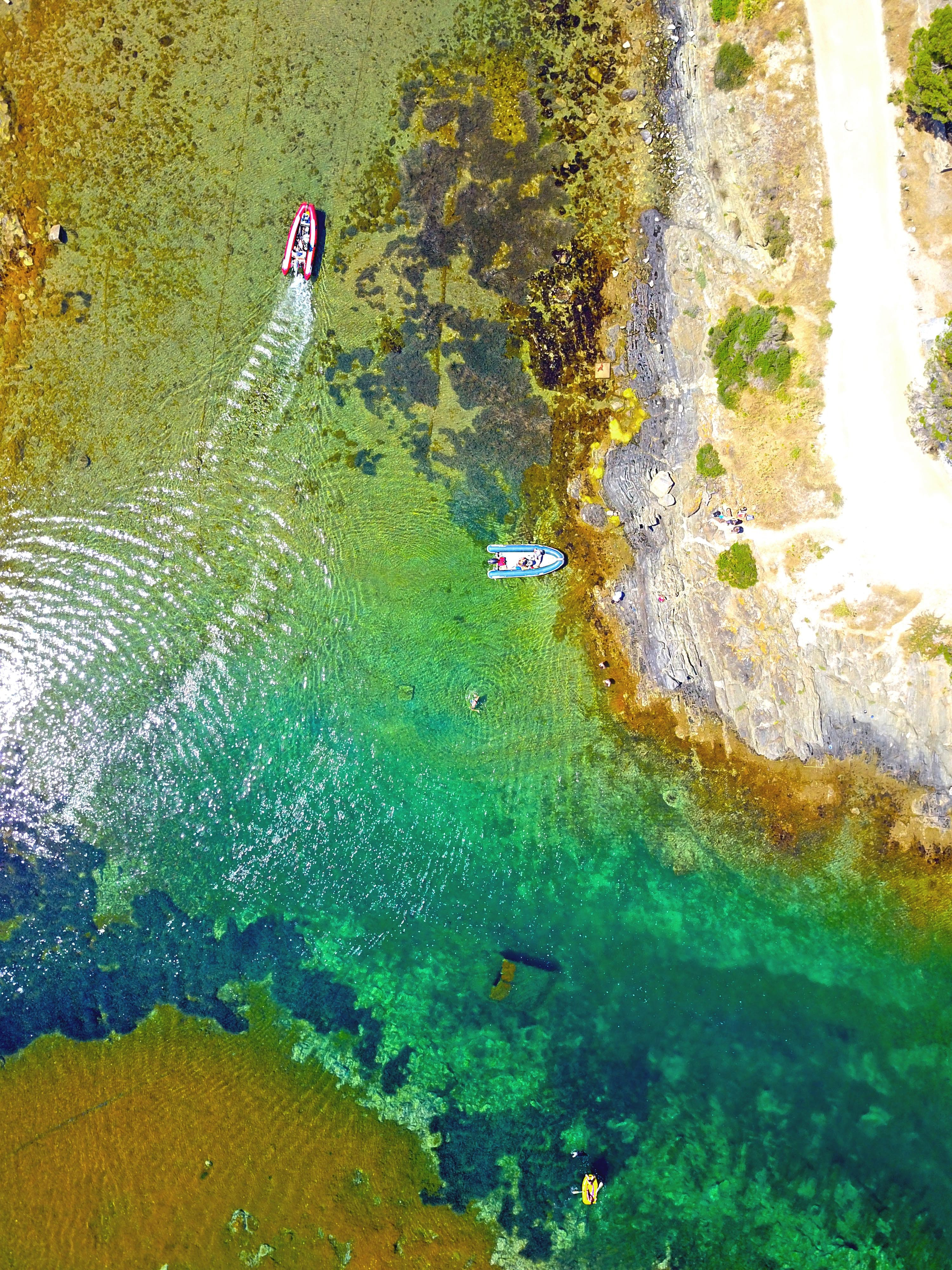 Drone view of boats in colorful shallow waters in Catalunya, Spain.