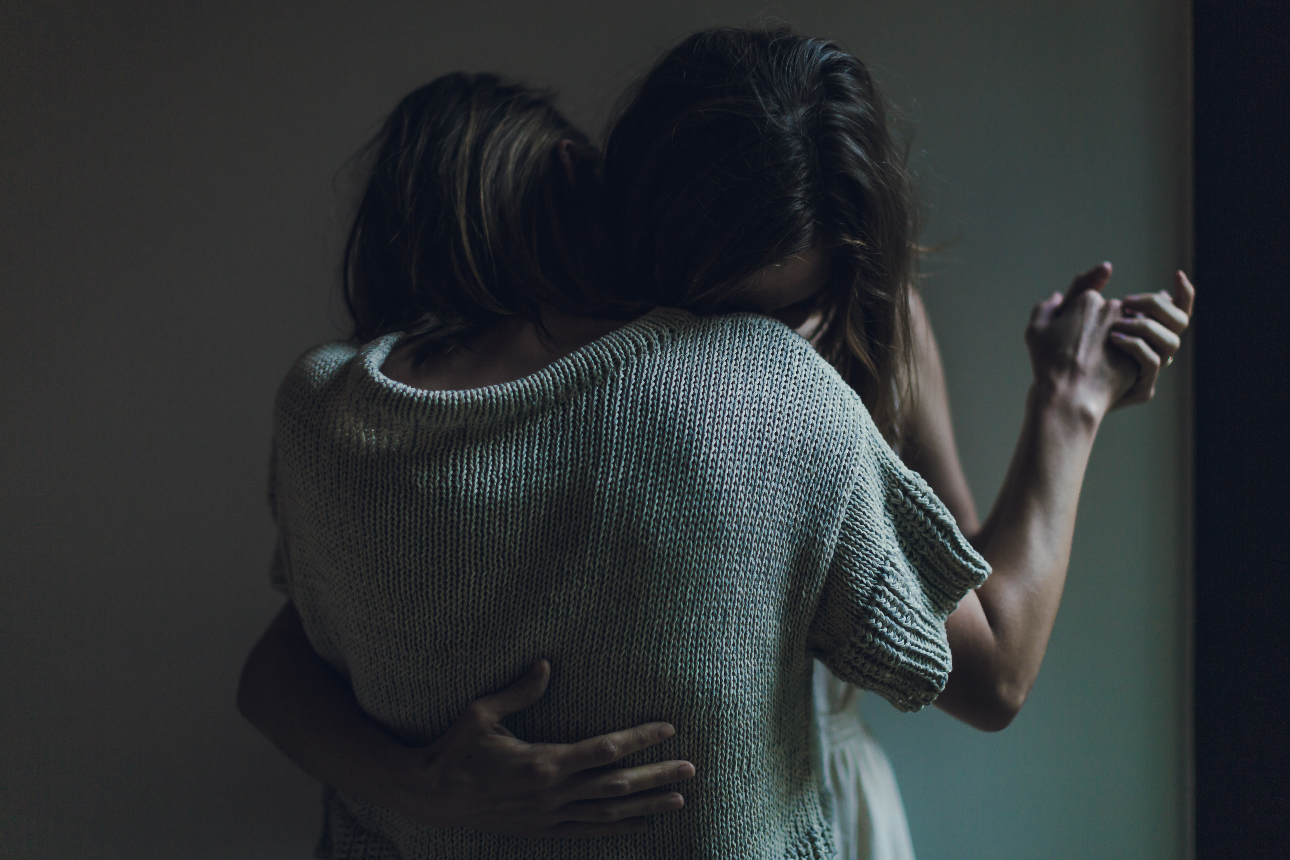 Two people holding each other close, dancing slowly in darkened room