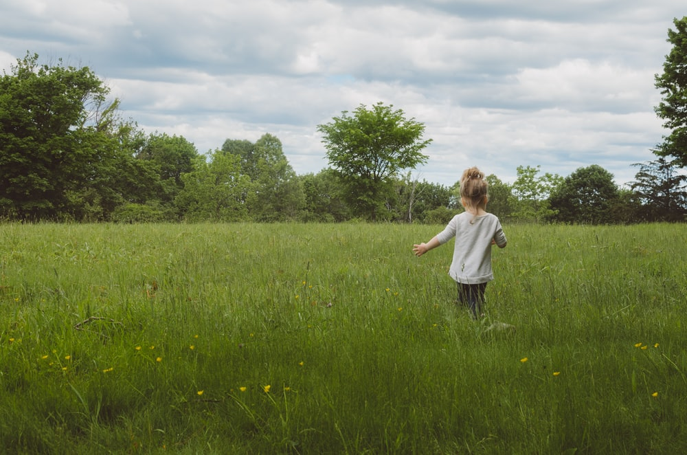 girl wearing white shirt on green grass