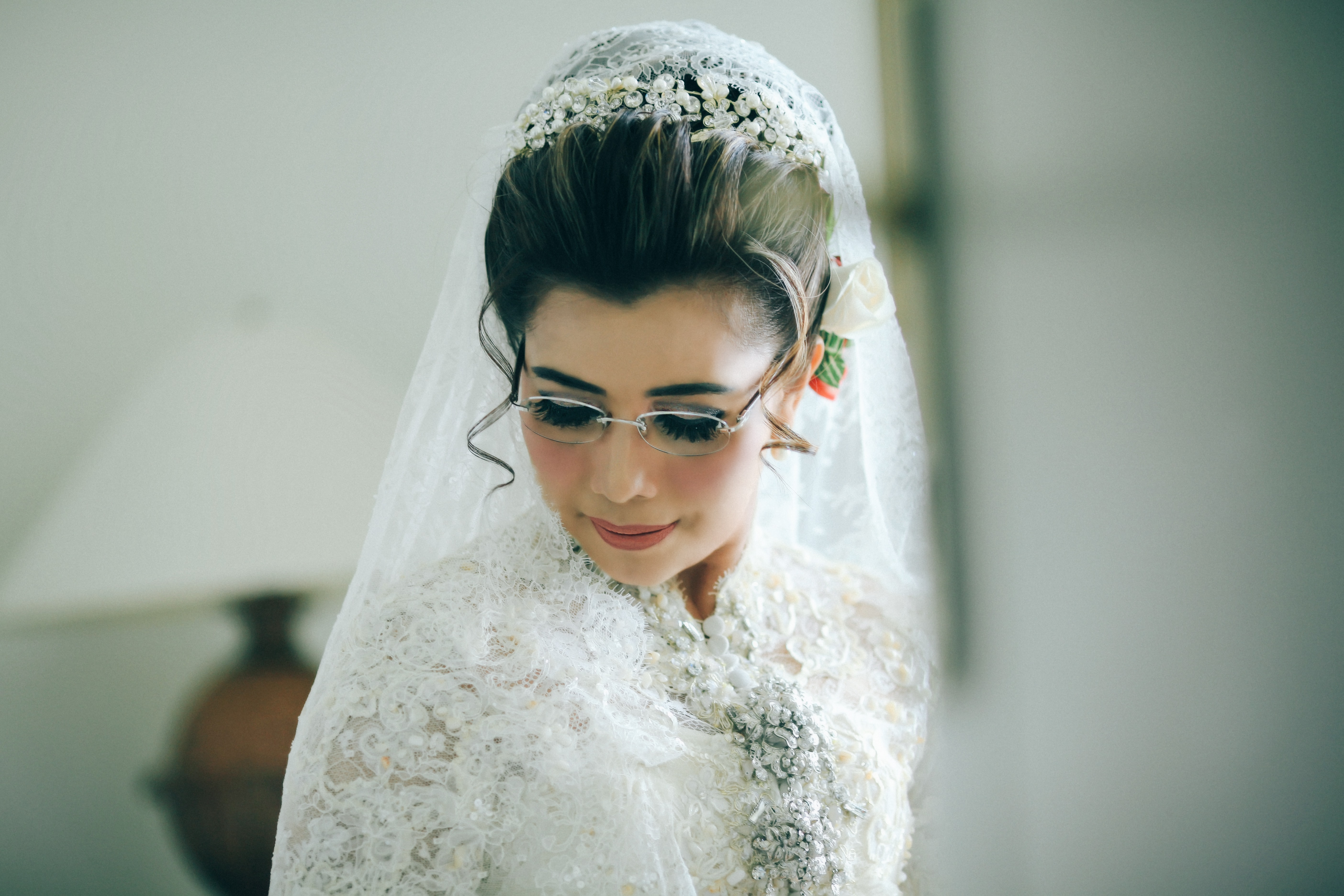 A bride in glasses and a lacy dress and veil looks downward
