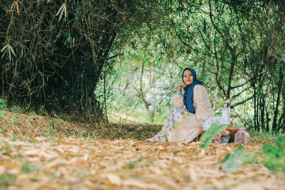 A woman in a blue headscarf and a floral dress smiles while sitting under a green arch