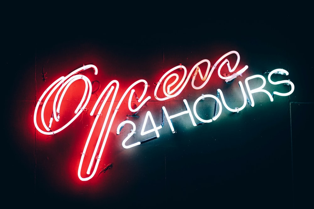 "An ""open 24 hours"" neon glowing in red and white"