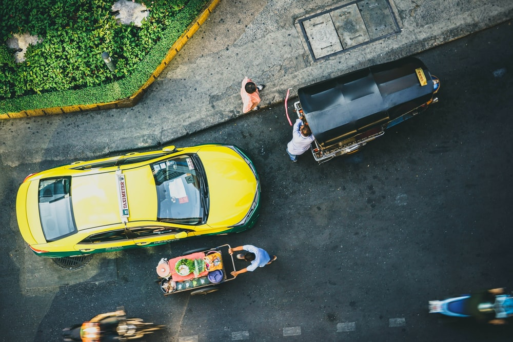 A top view on a Bang Wa street with a taxi, motorbikes and an auto rickshaw