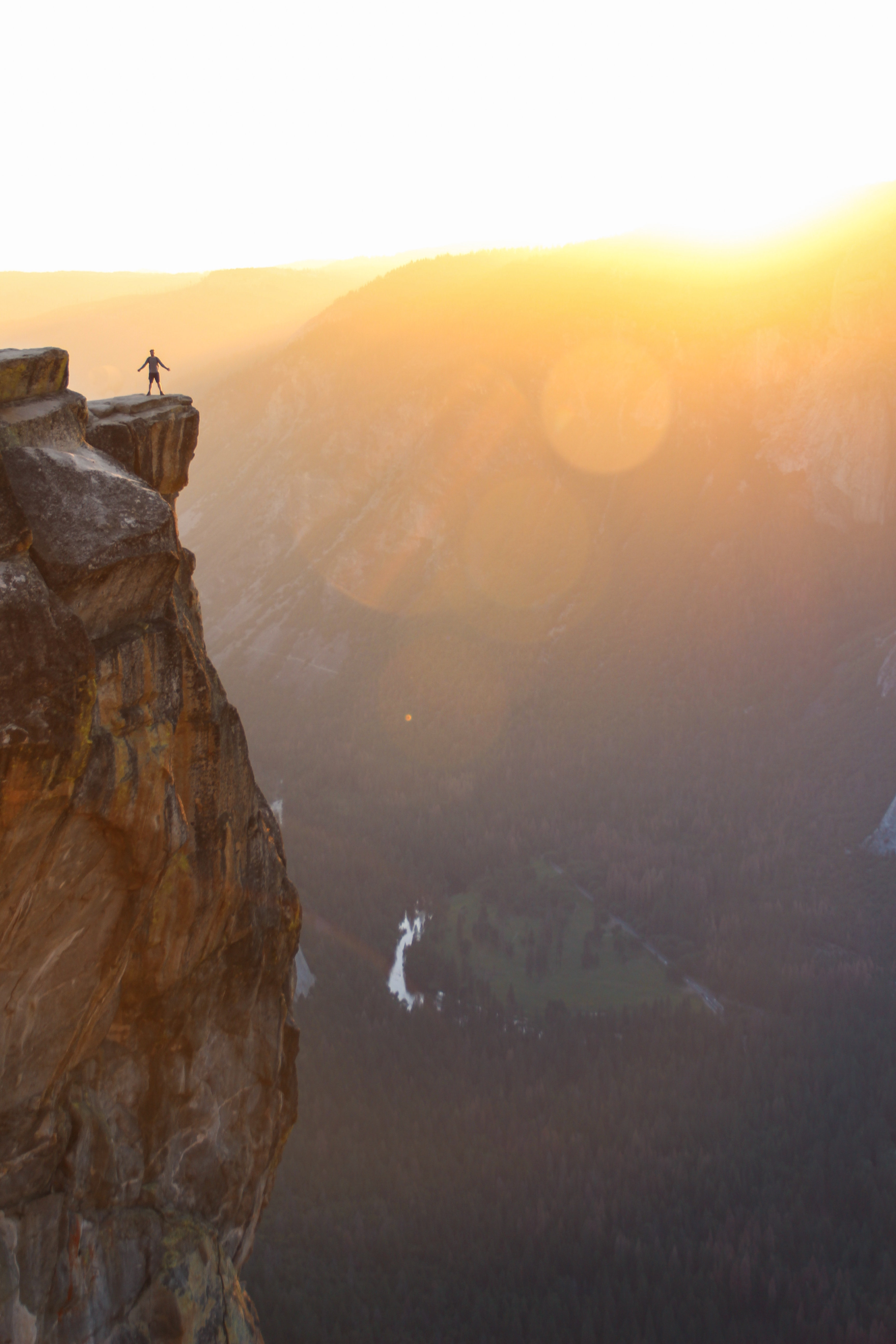 Person with arms stretched wide standing by the ledge of a cliff during sunrise in Yosemite Valley