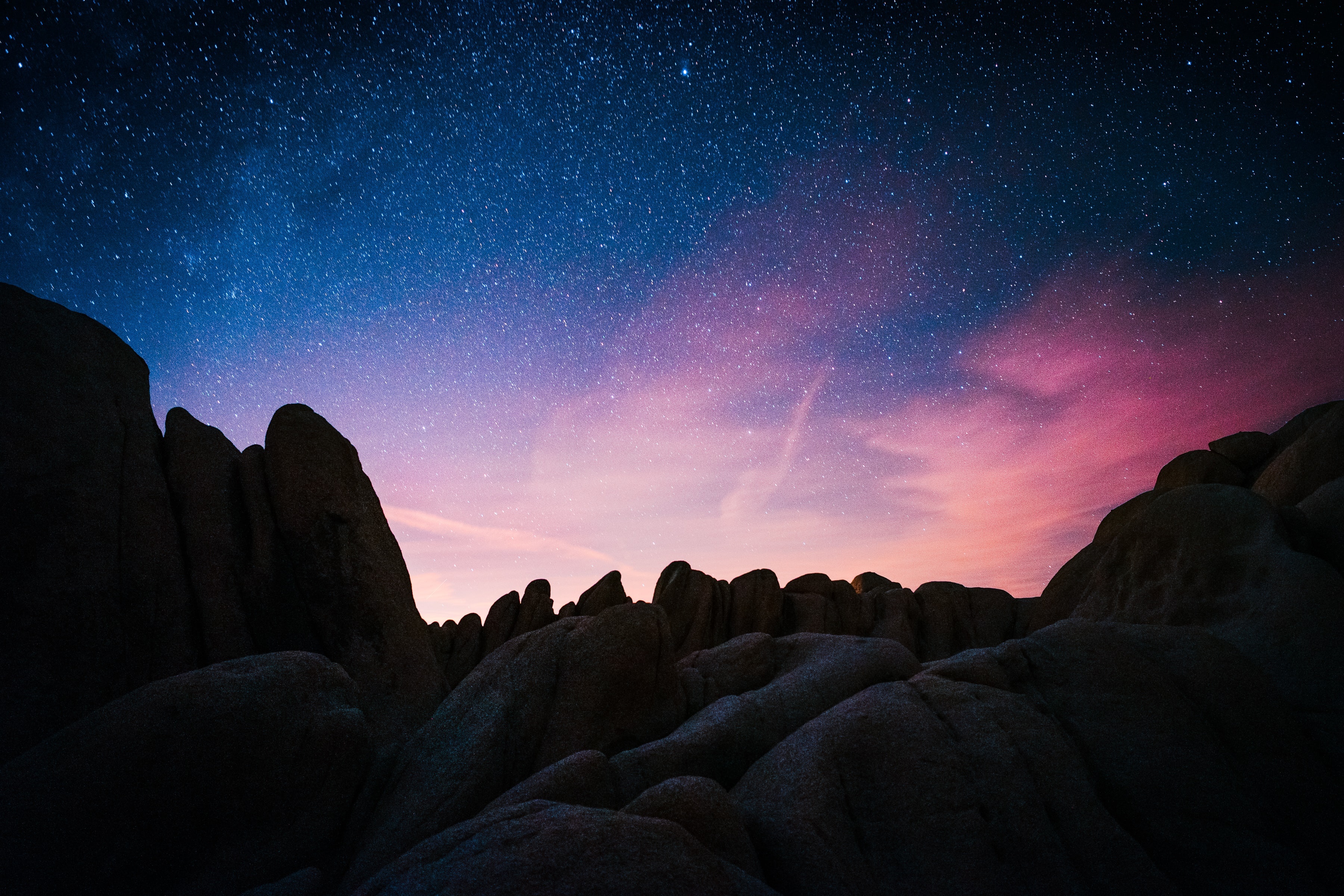 The sky full of stars with blue and pink hues over the rock formations.