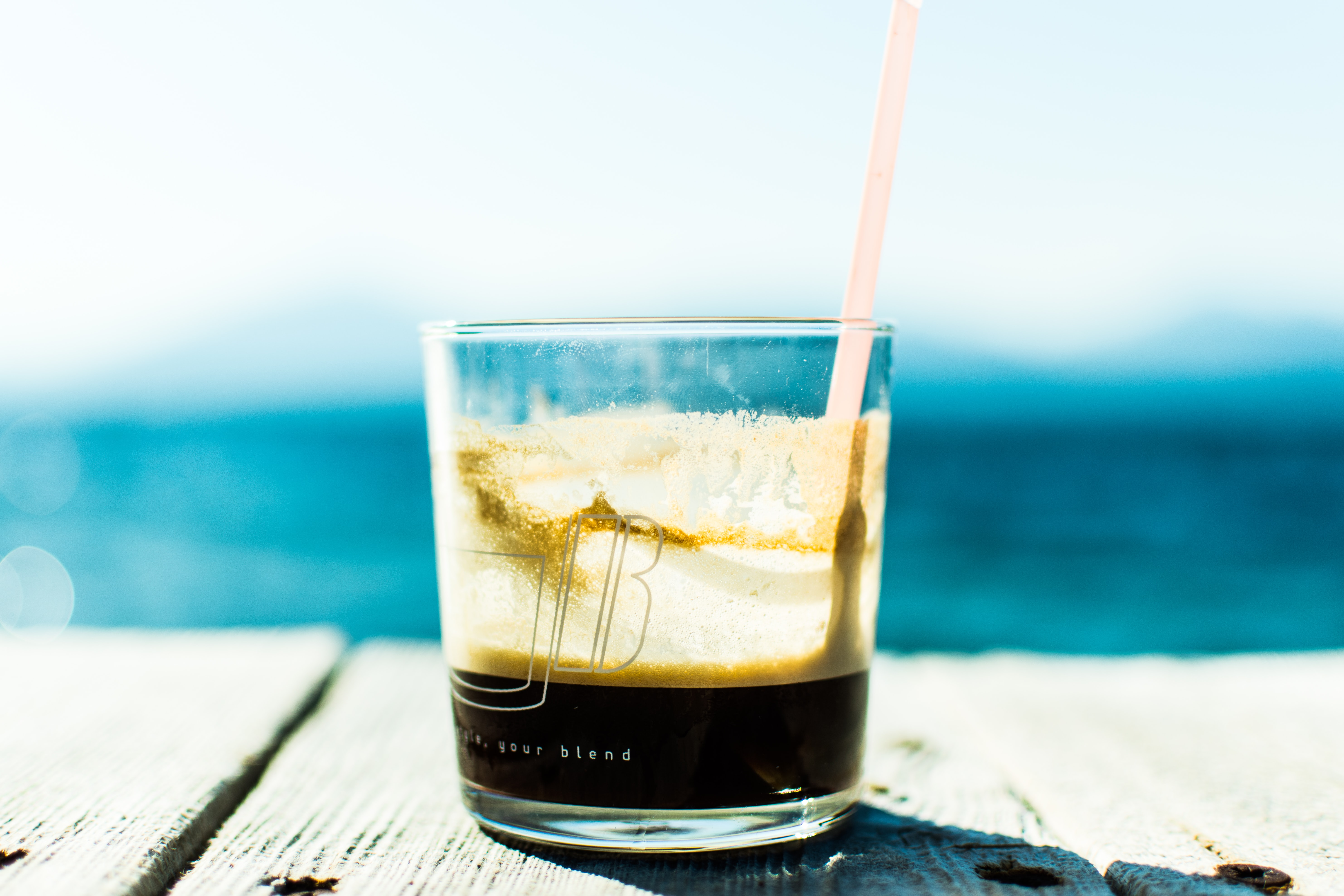 The macro view of a glass cup containing coffee and a straw on a table in Greece