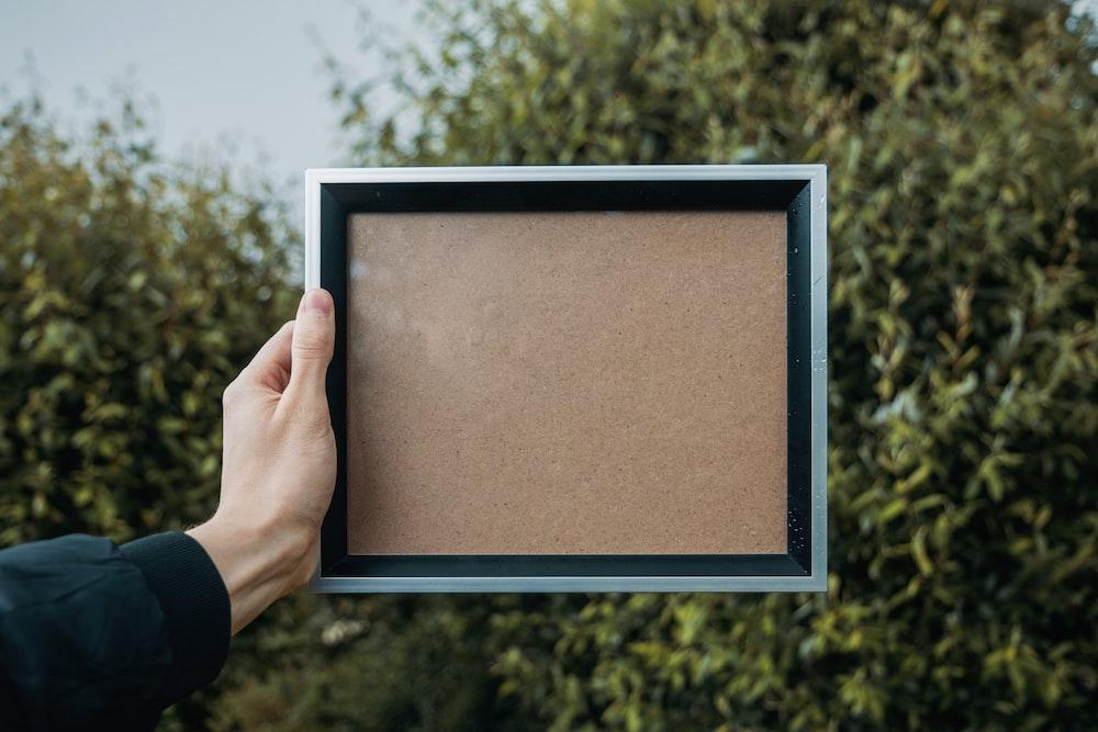 person holding rectangular white and black frame