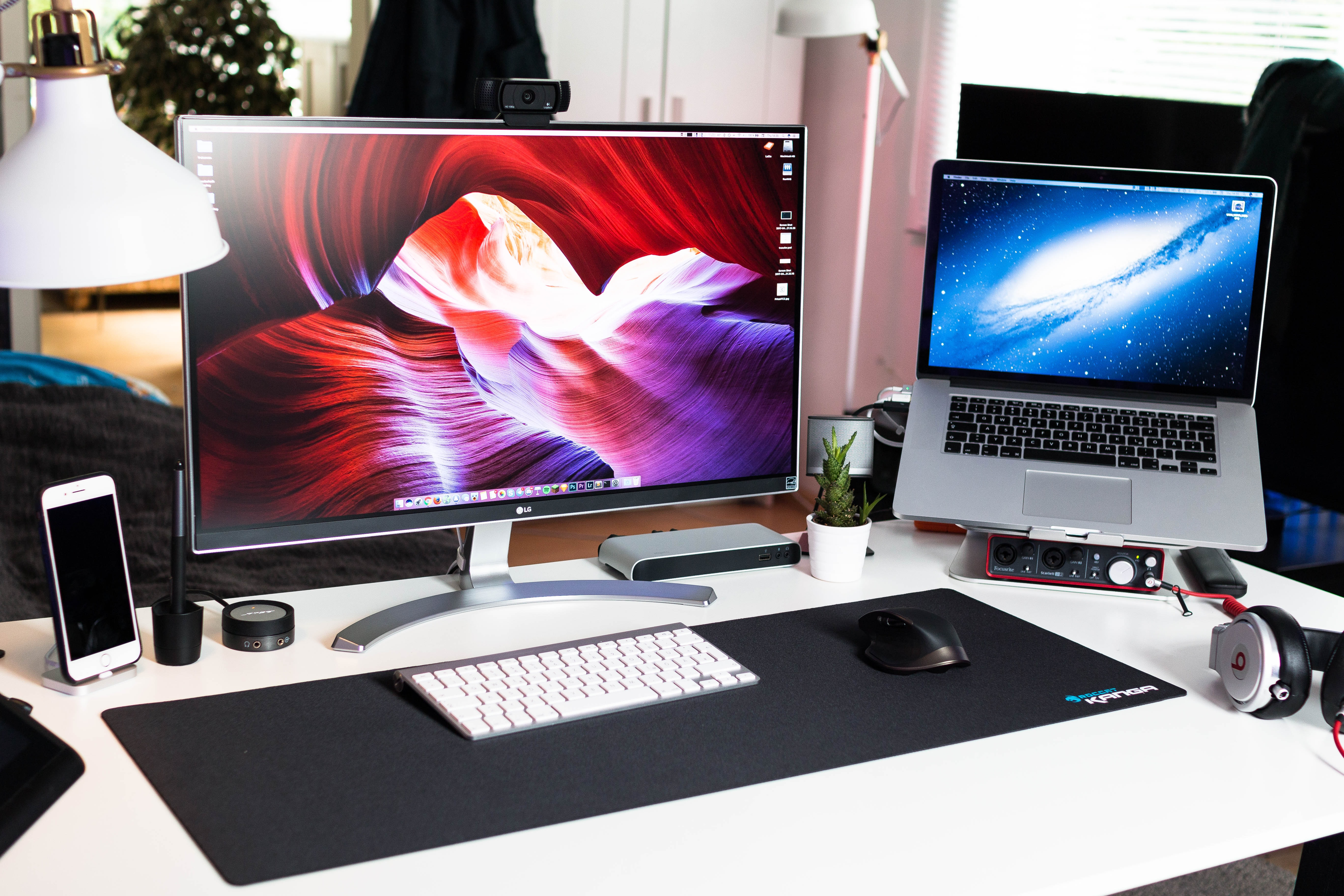 A computer workspace with a display, a MacBook and various accessories