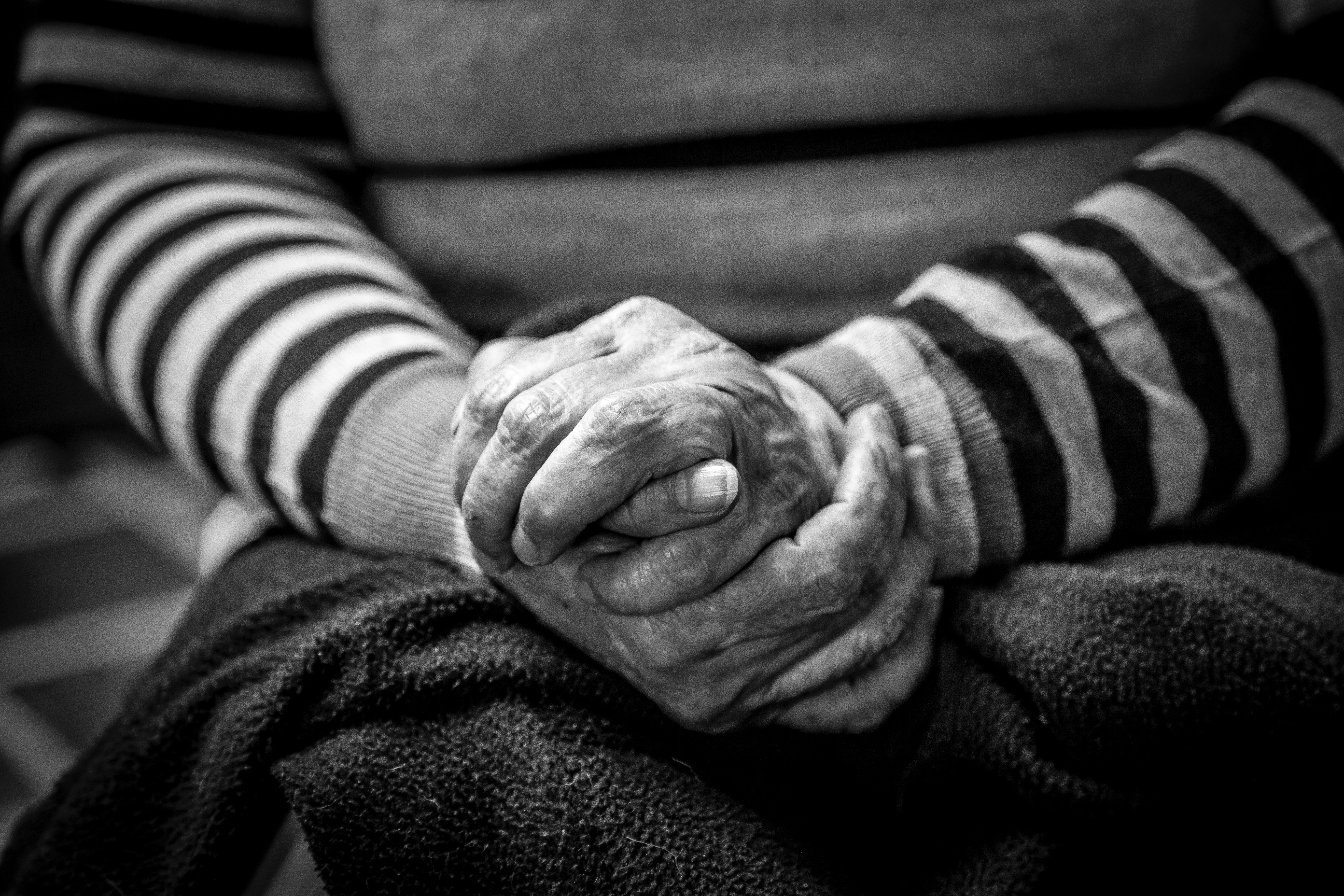 An old south American woman wearing a striped shirt folding her wrinkled hands together in Bogotá.