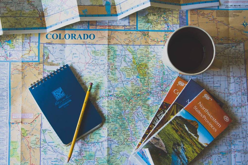 books and pencil on map