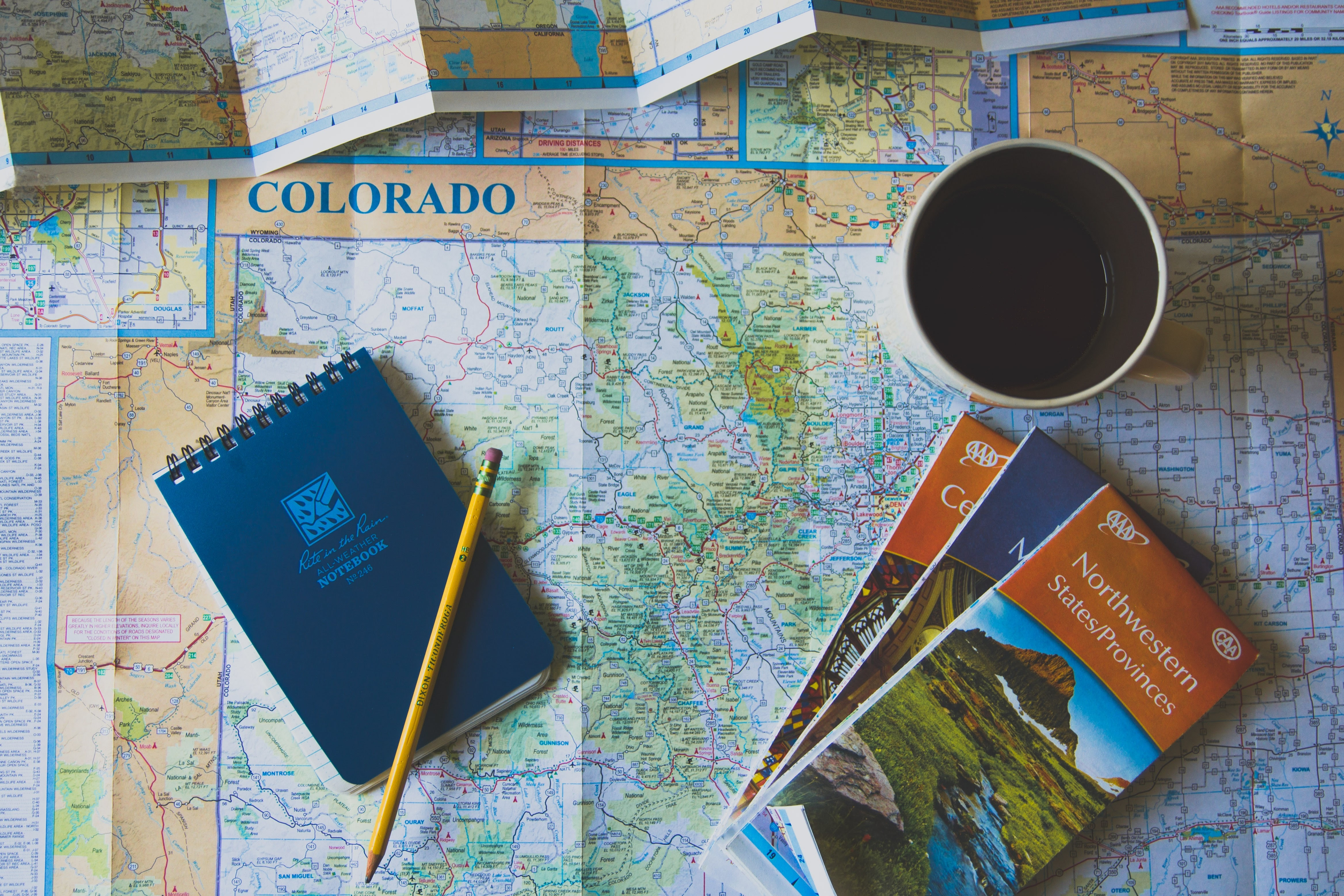 Rite in the Rain notebook, coffee, pencil, and three atlases sit on a map of Colorado