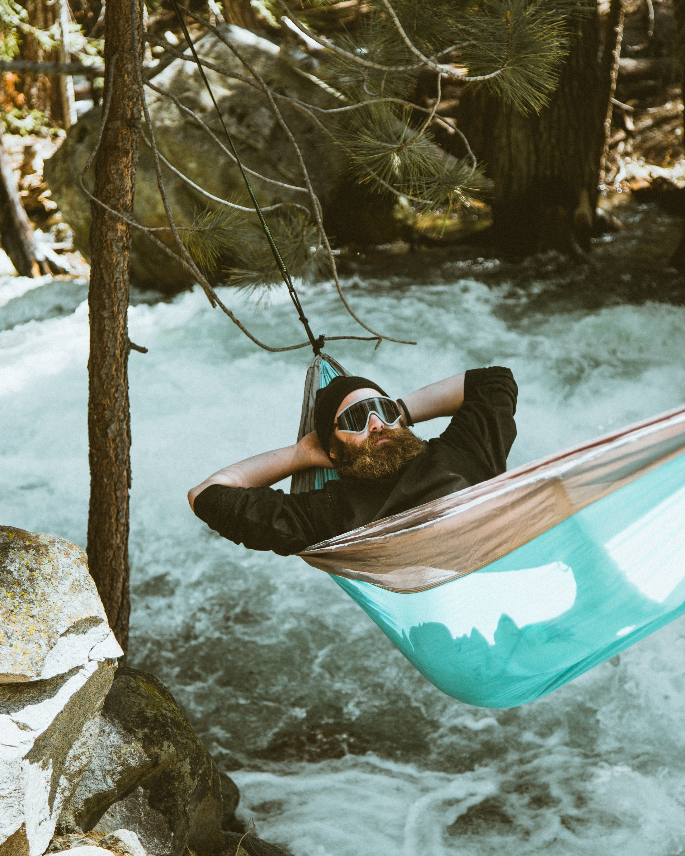 A man with a beard wearing goggles and a hat, laying on a blue hammock over a river in the forest