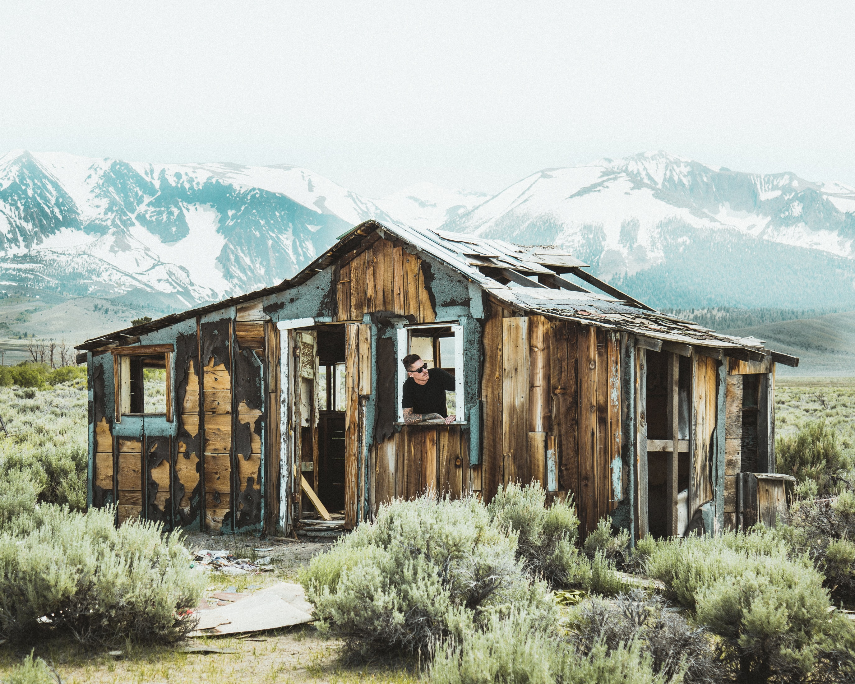 A man in sunglasses looks out of a dilapidated cabin in the mountains