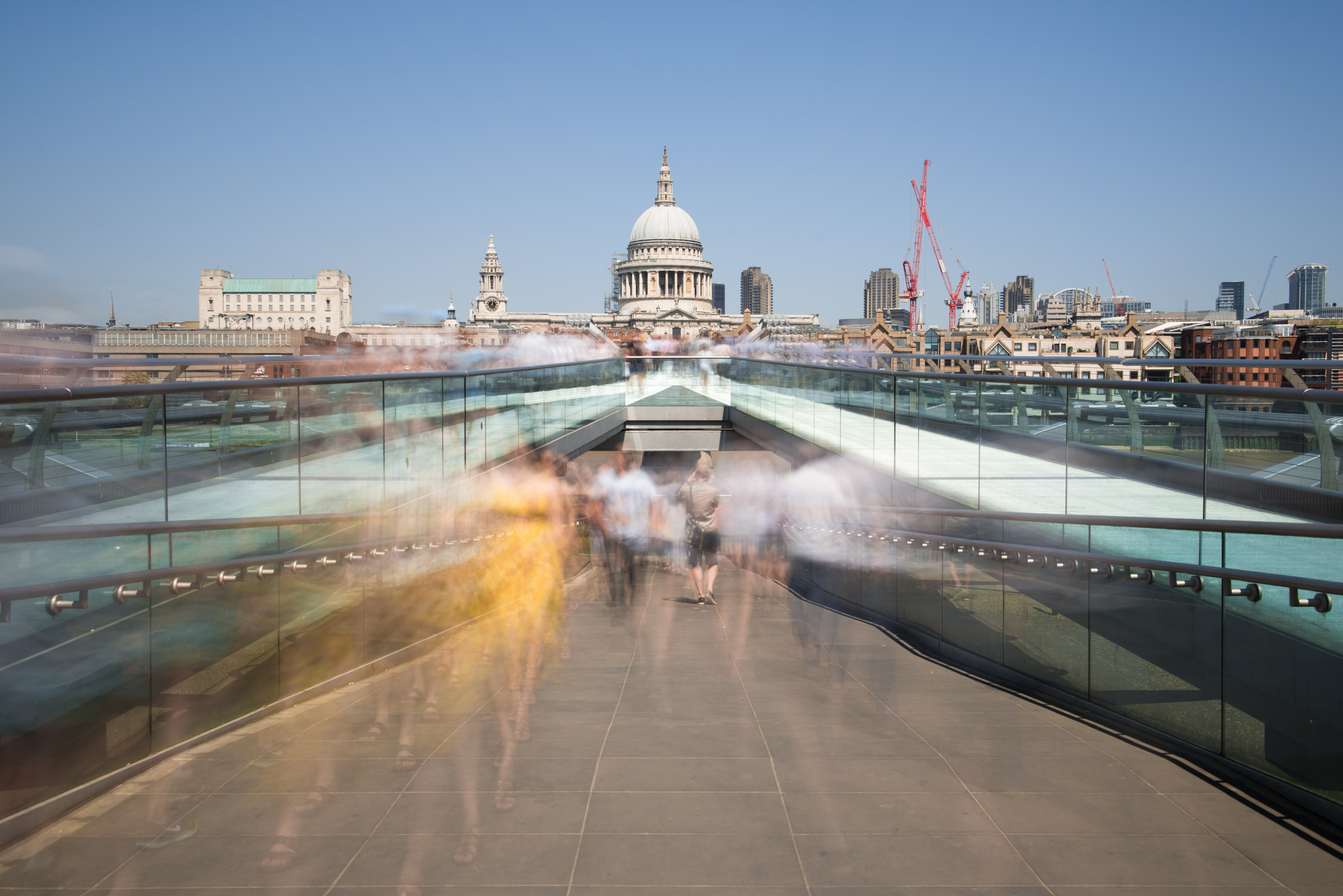 Long-exposure shot of people on the Millennium Bridge with a view on St. Paul's Cathedral