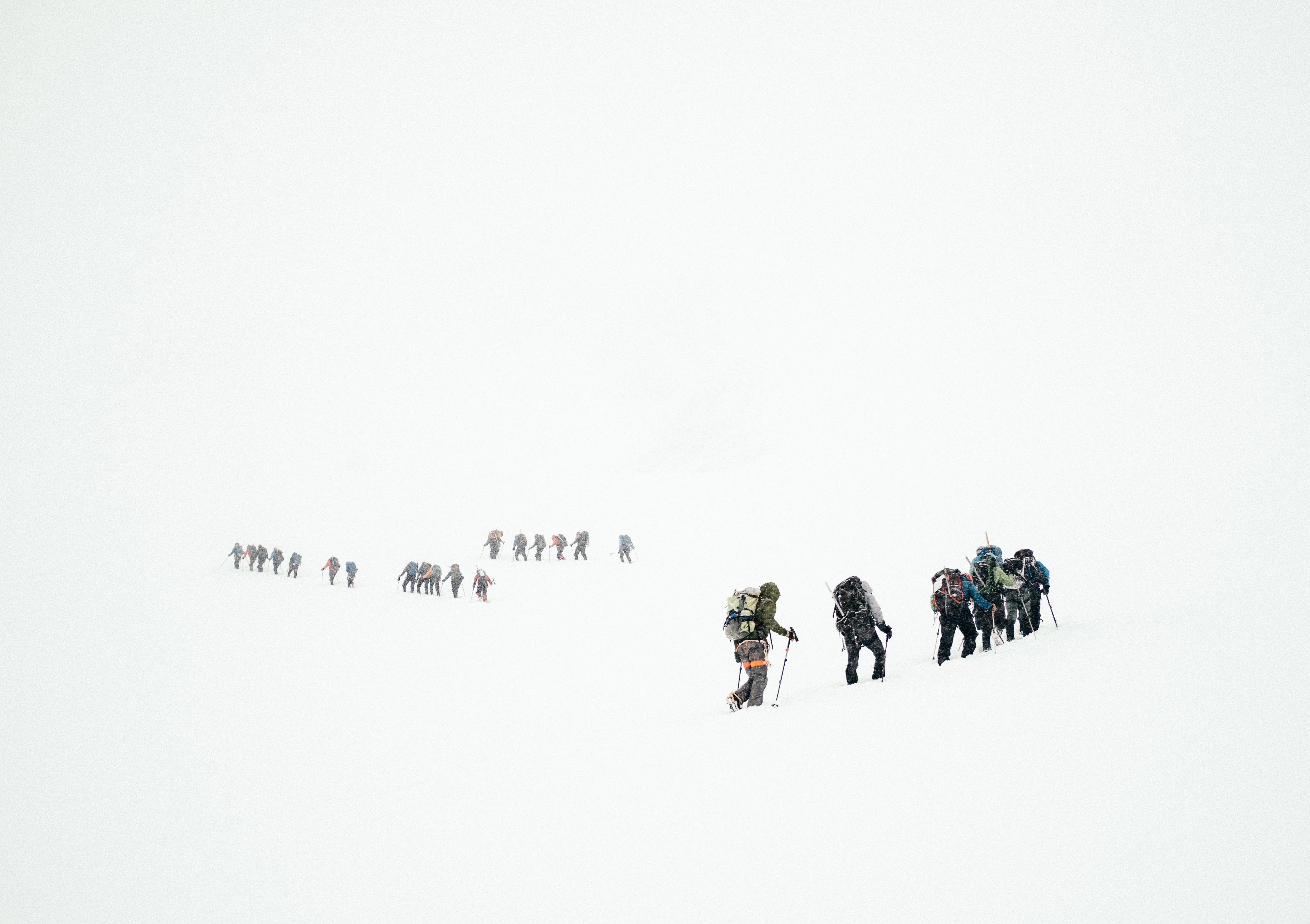 Small groups of mountaineers with heavy backpacks in a snowy wasteland