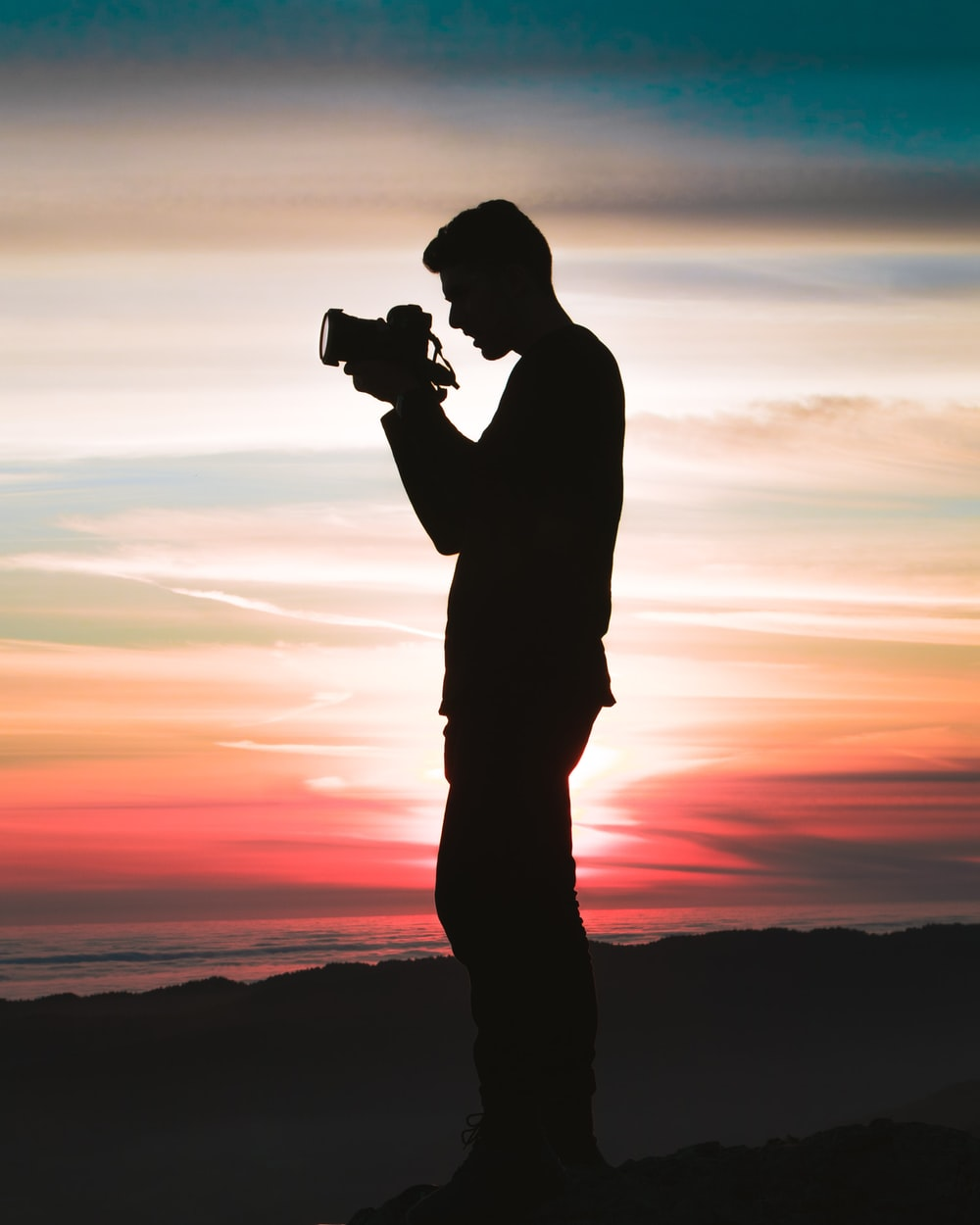 silhouette photo of man holding camera