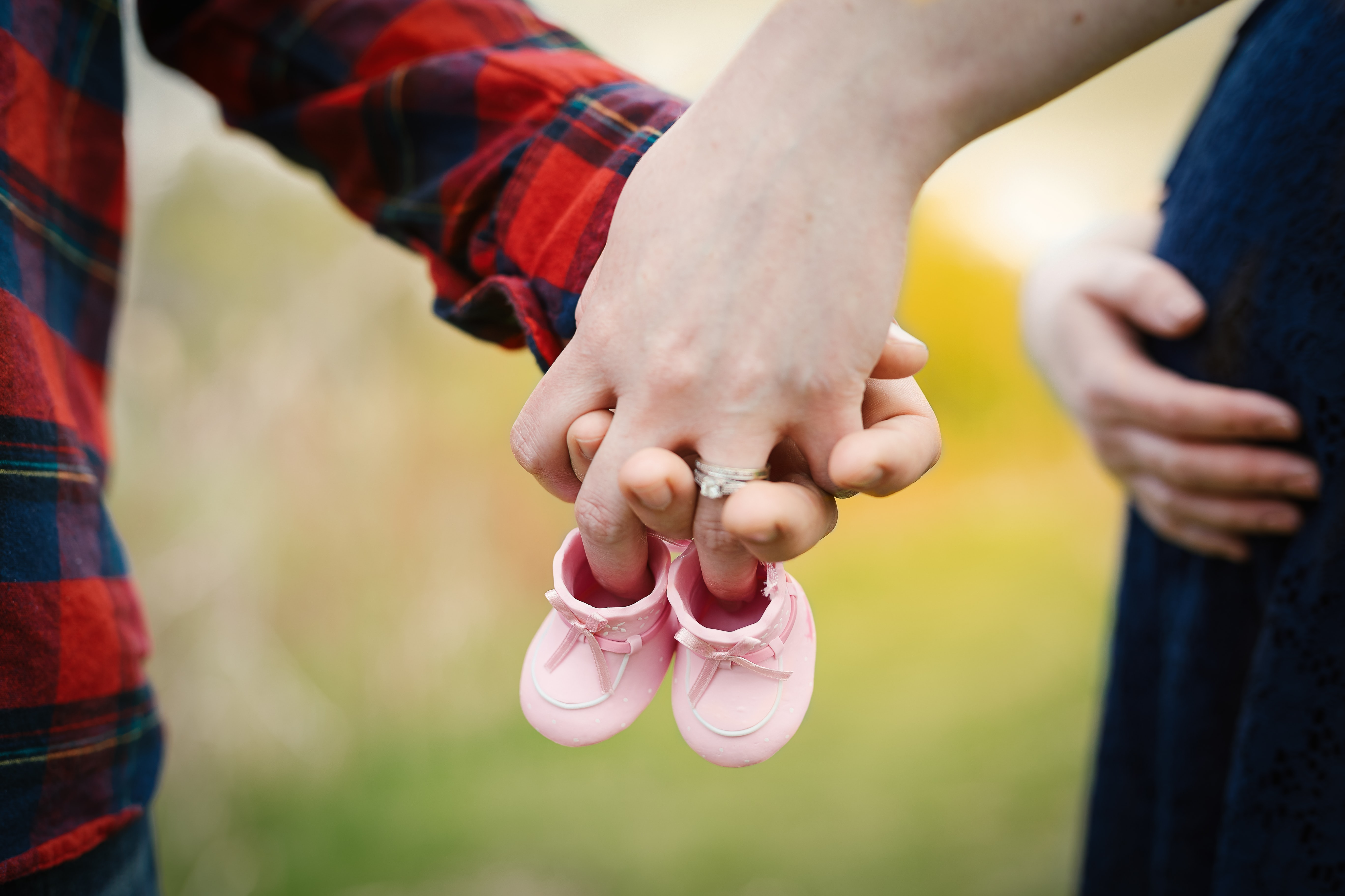 Pregnant woman holds her belly with one hand, her partner and baby shoes in the other