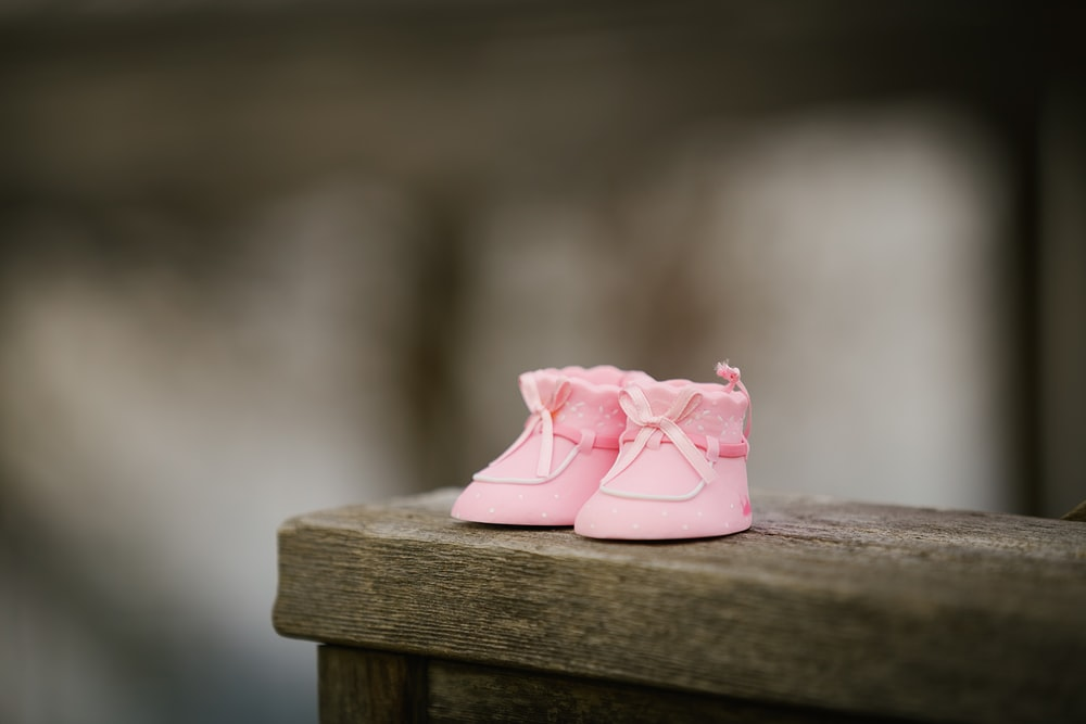 selective focus photography of pink shoes on wooden bench