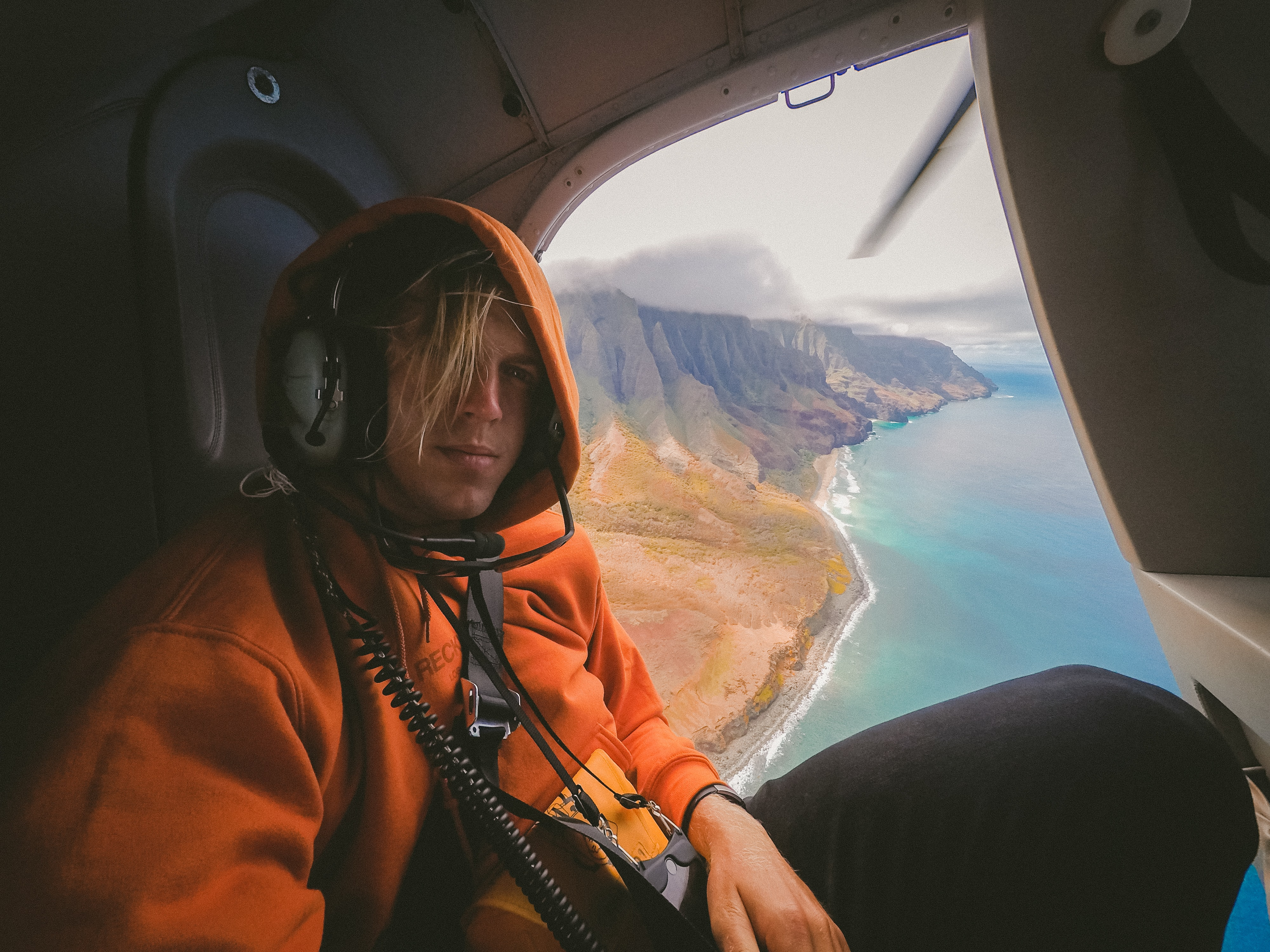 A male passenger in a helicopter flying over the shore of Kauai.