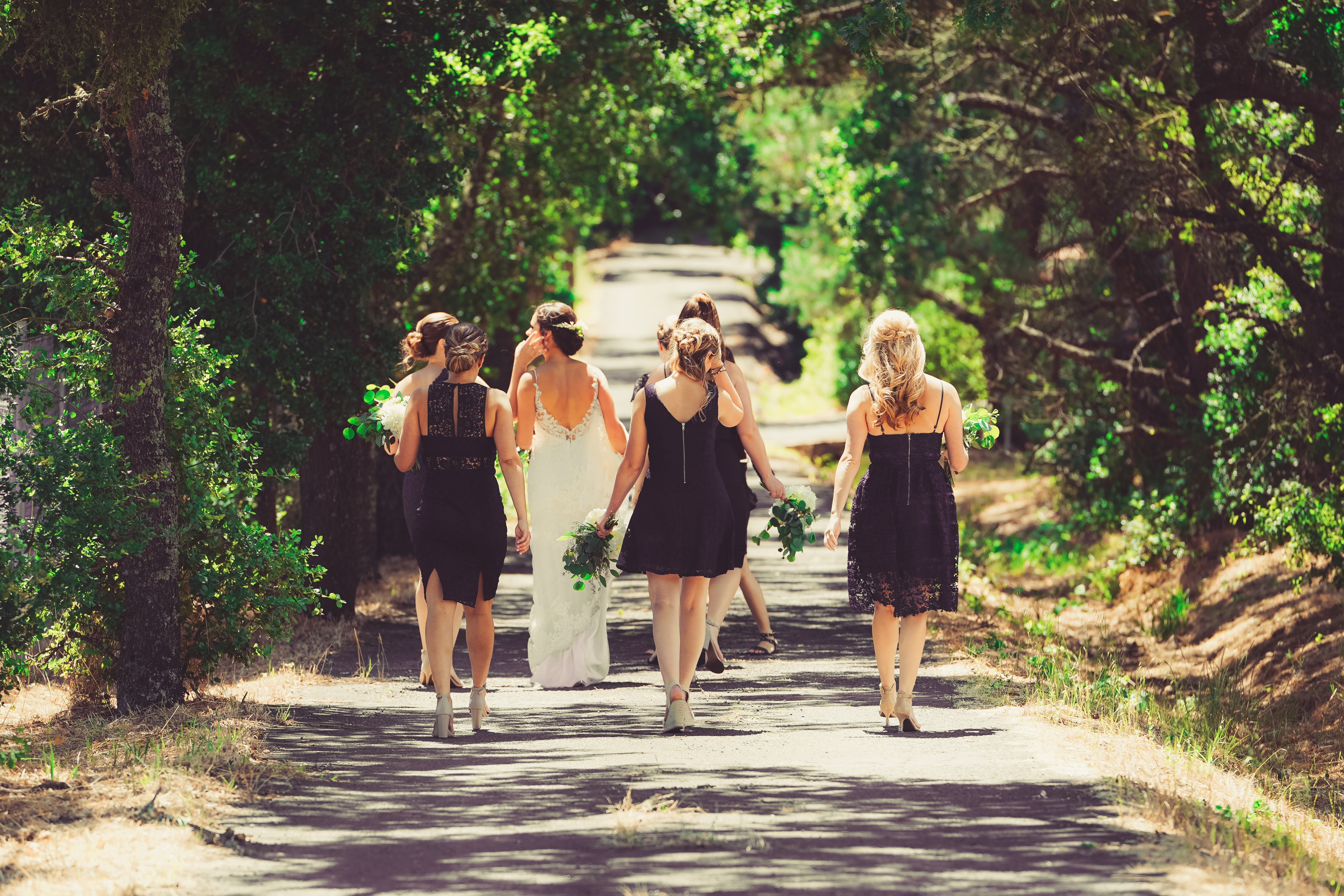 Bride and her bridesmaids walking down a country road for wedding photos