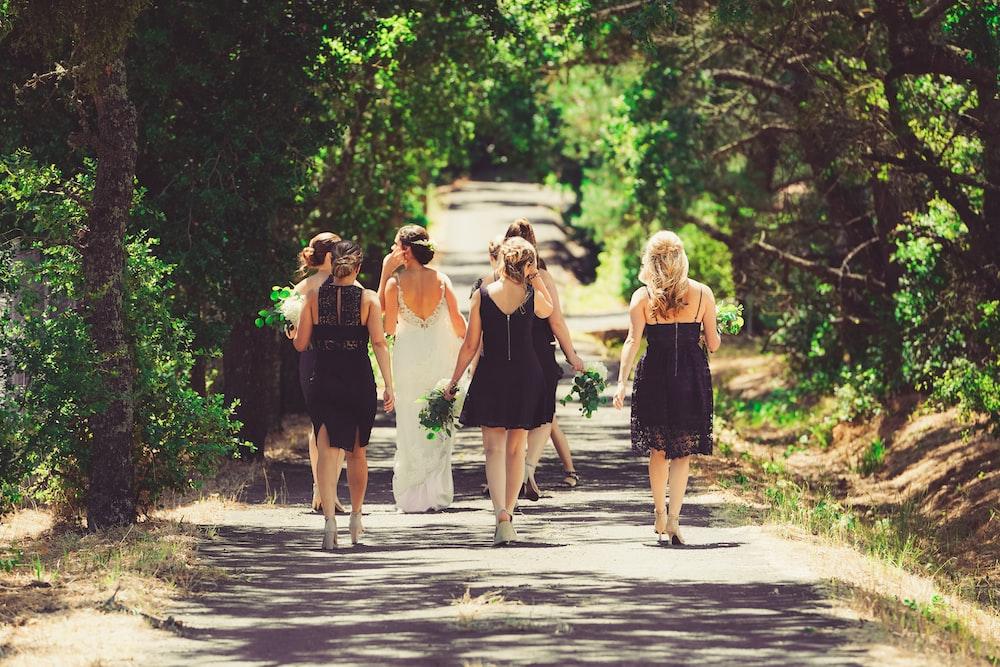 bride and bridesmaid walking on street between green trees