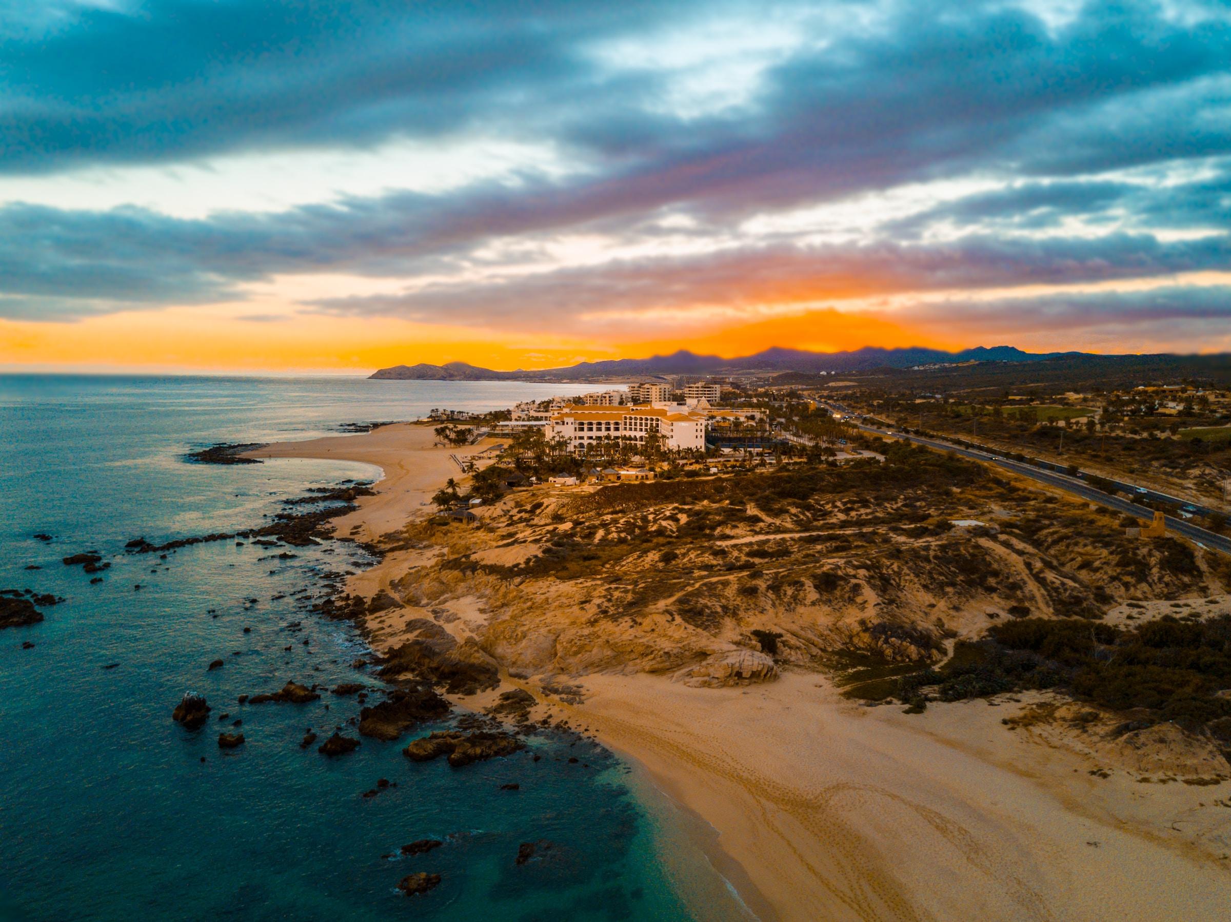 An orange sunset over a quiet coastal beach in San José del Cabo