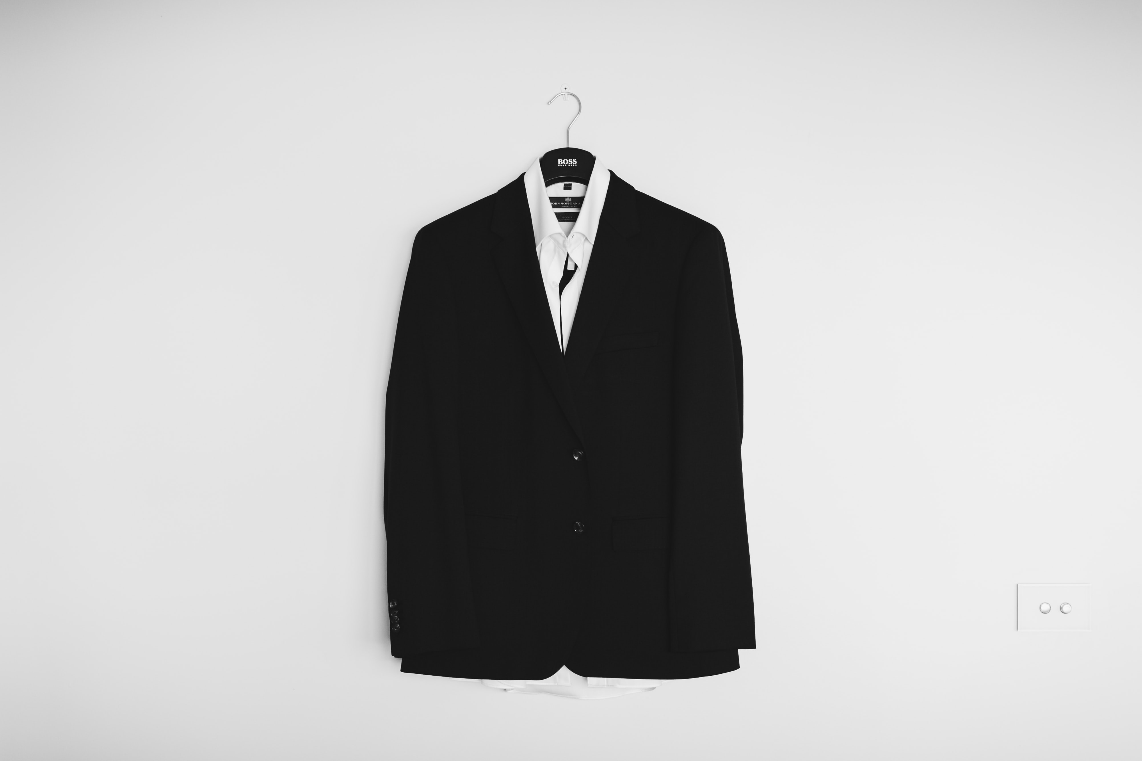 A black suit jacket on a hanger on a white wall