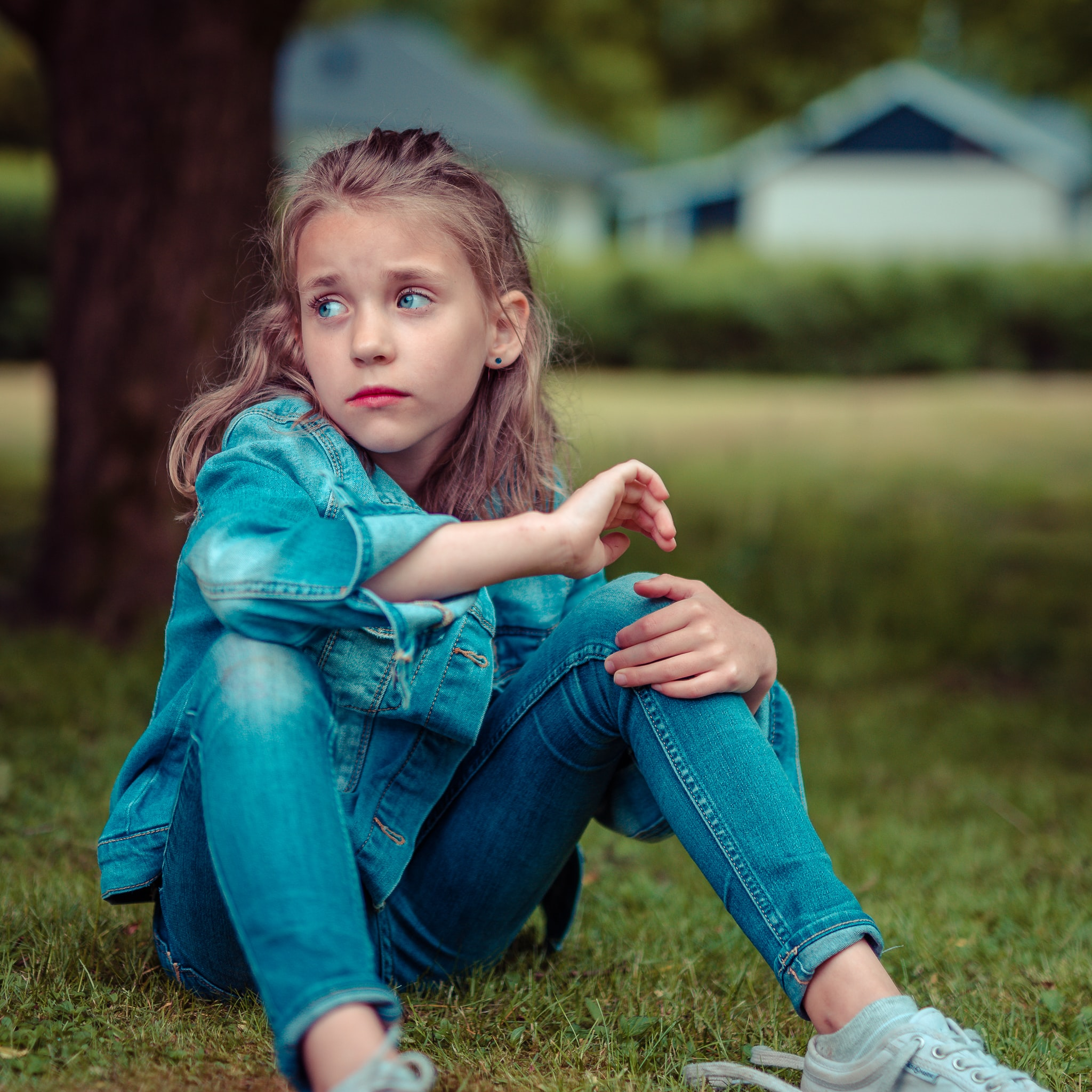selective focus photography of girl sitting near tree