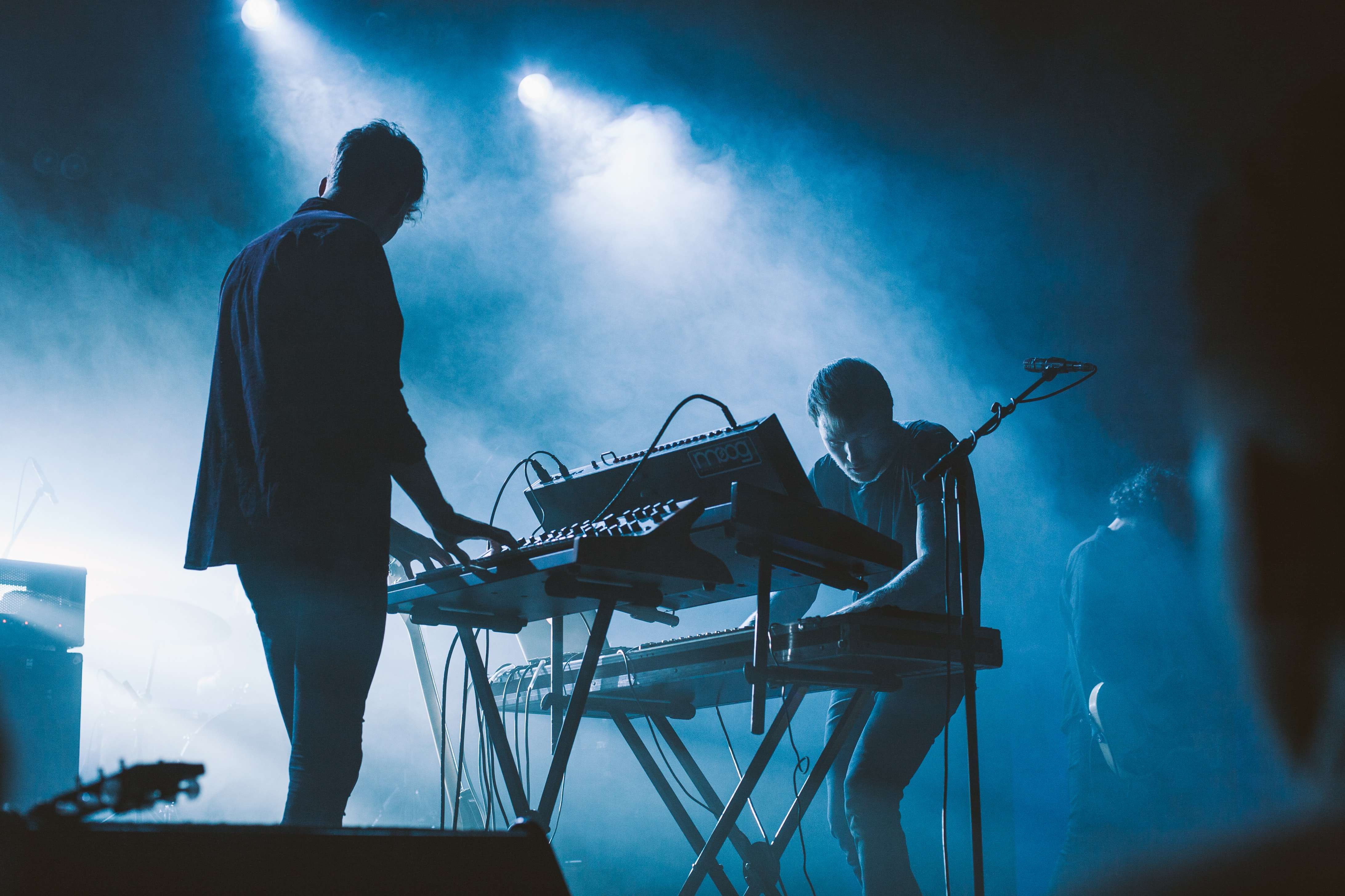 Electronic musicians play a show in blue stage lights and smoke