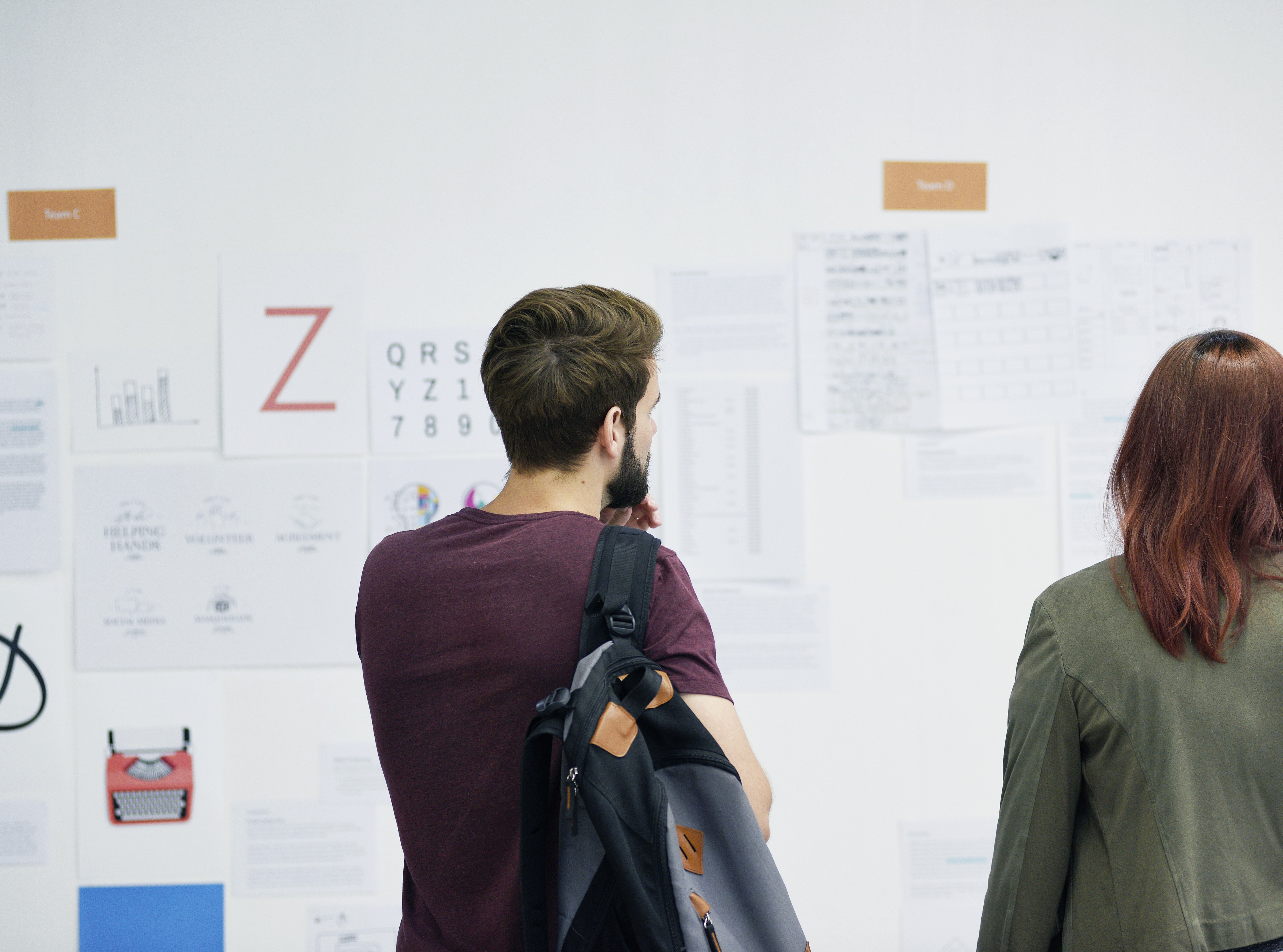 A man and a woman looking at posters on a white wall