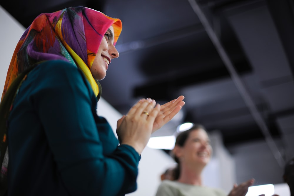 A woman in a colorful headscarf clapping and smiling