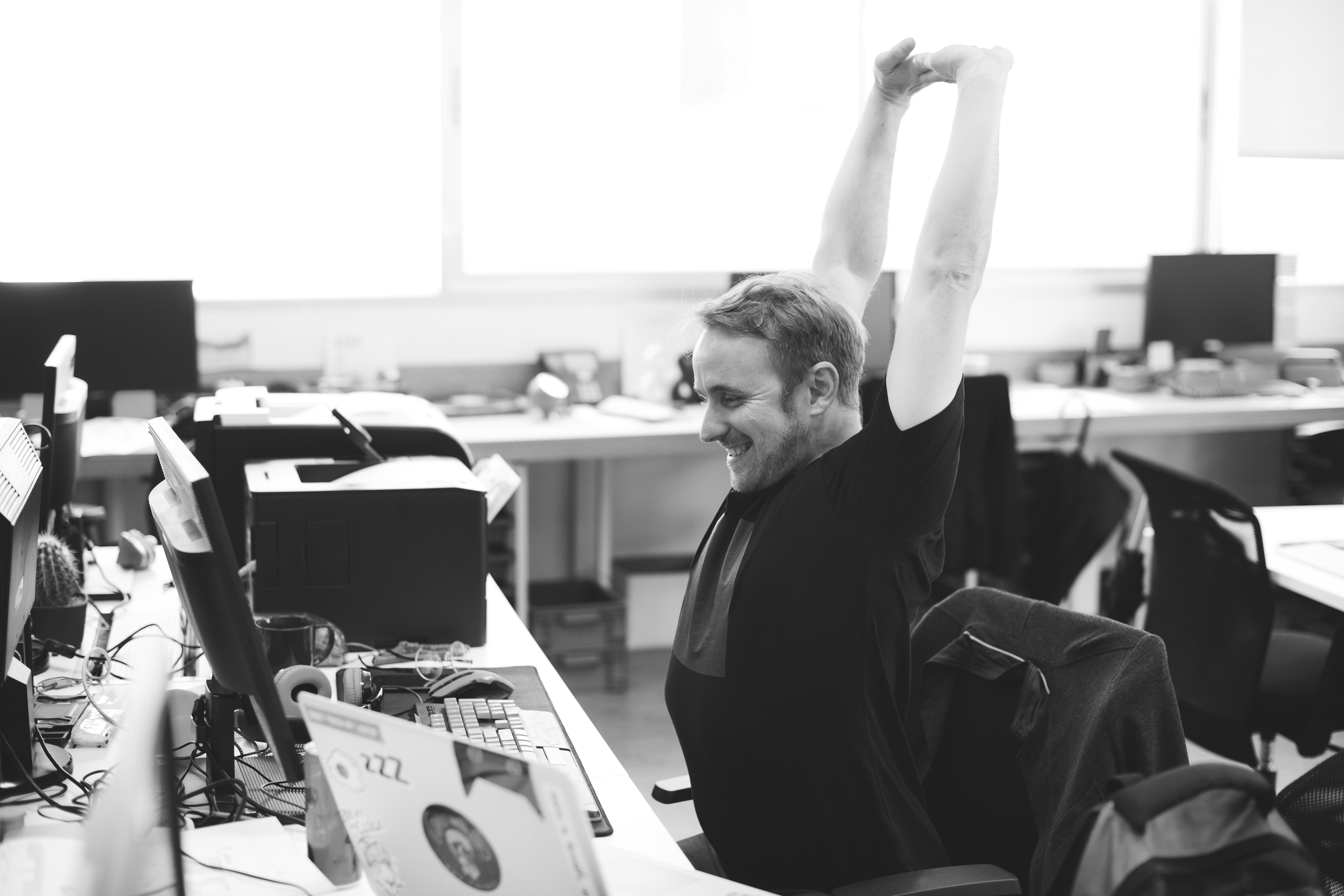 grayscale photo of man stretching his arm
