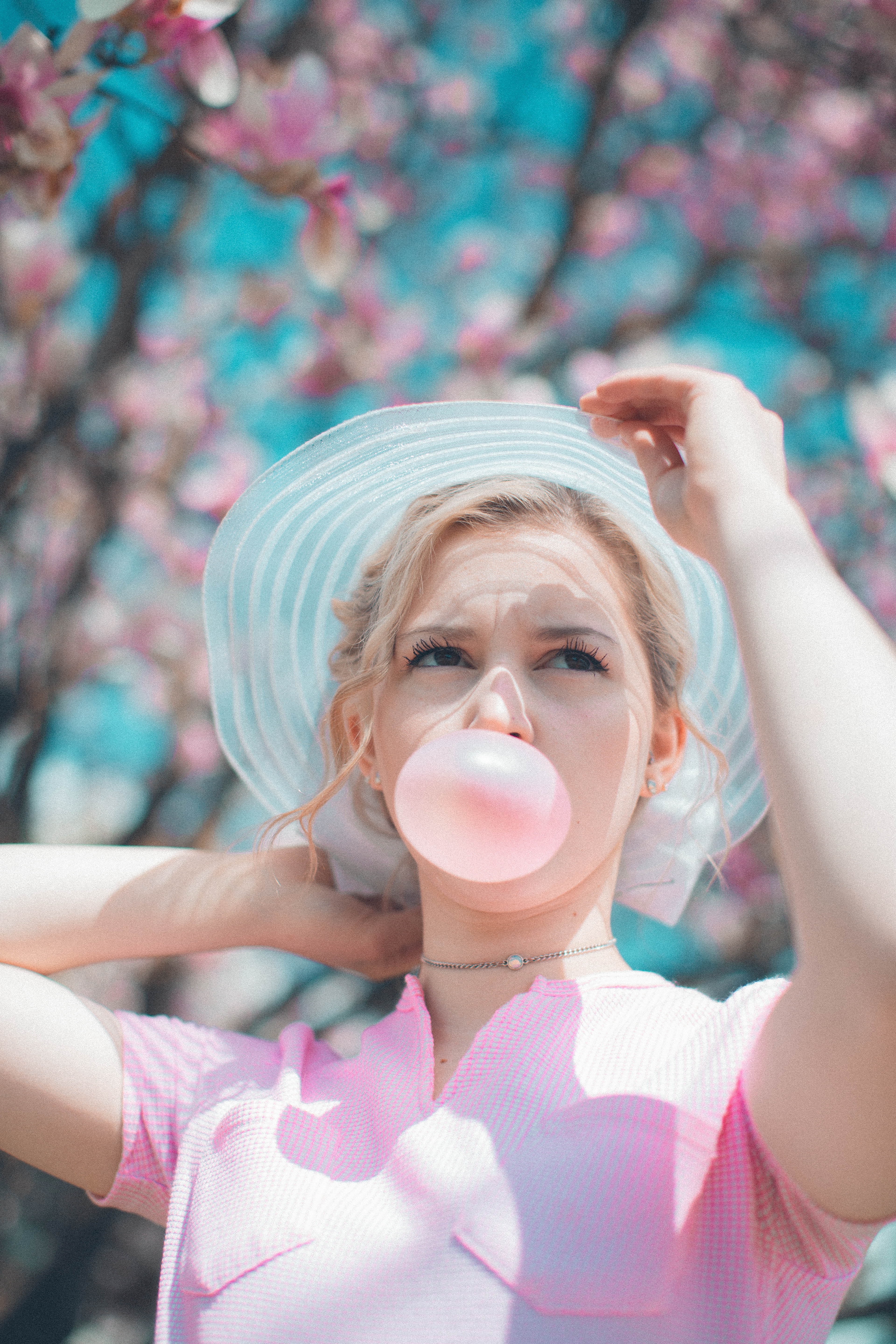 woman under pink tree blowing chewing gum