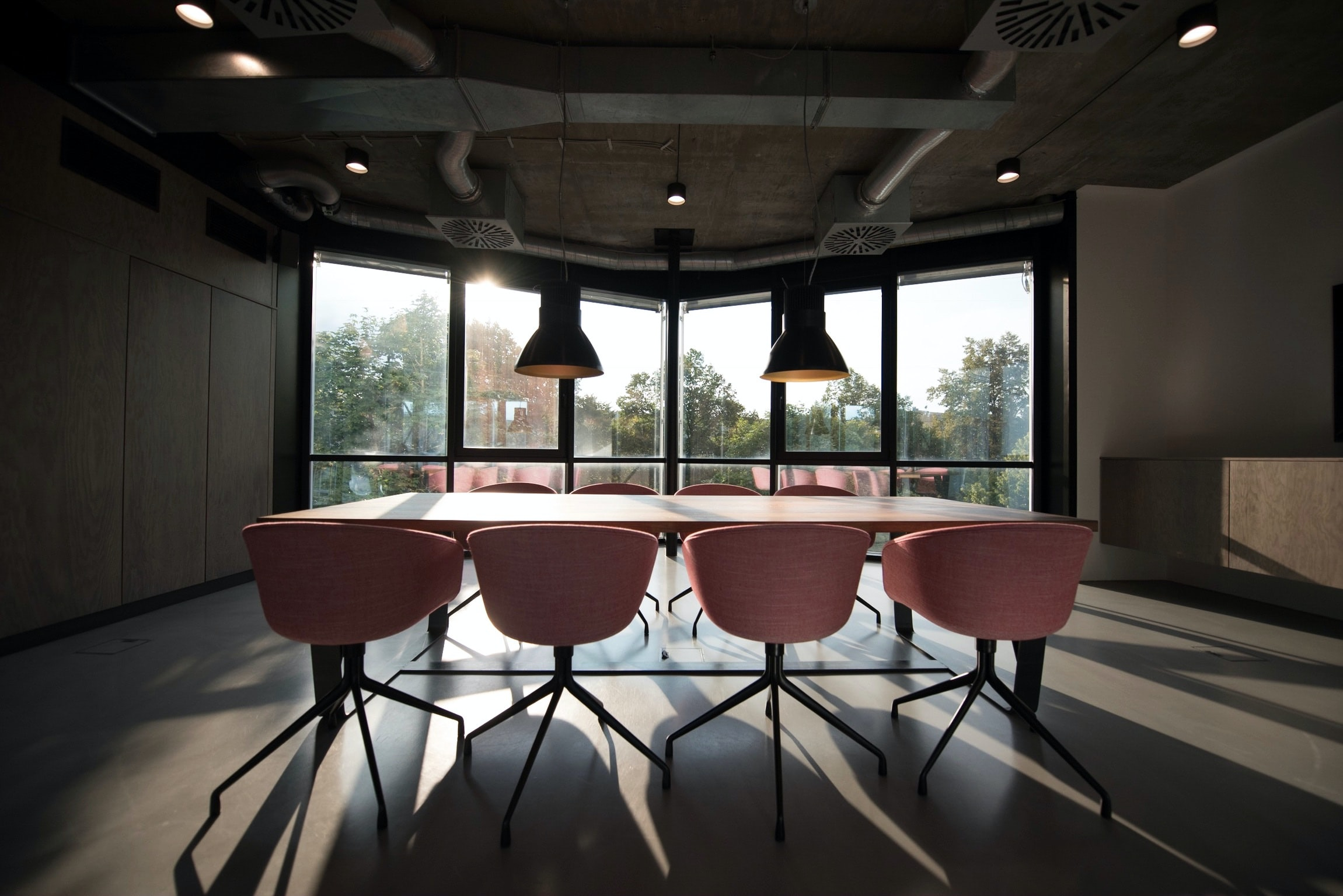 An unfurnished conference room with a table and eight pink chairs