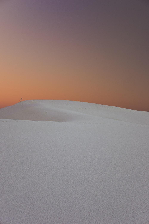 person walking in the desert dunes