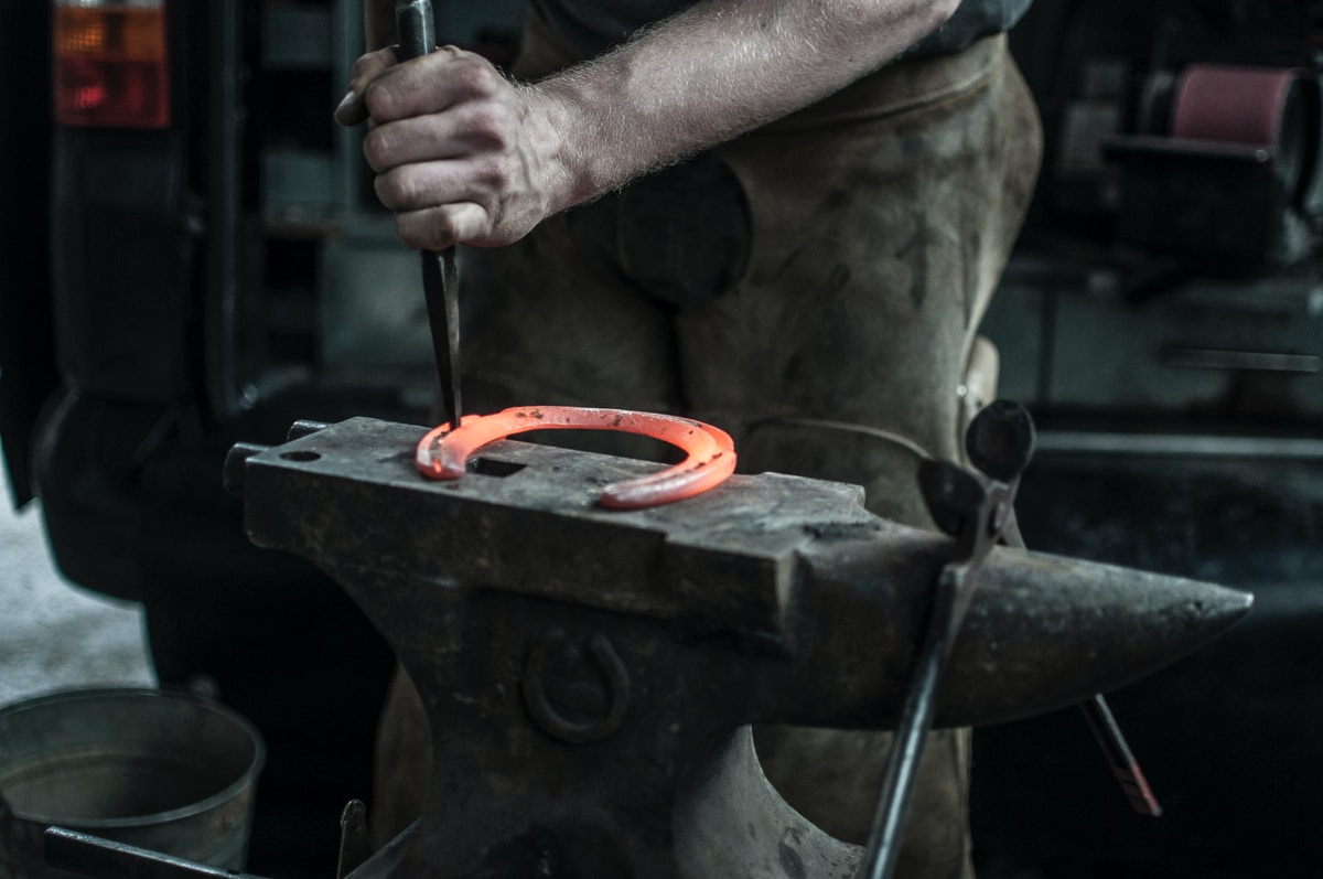 Photograph of a man working on a red hot horseshoe on an anvil.