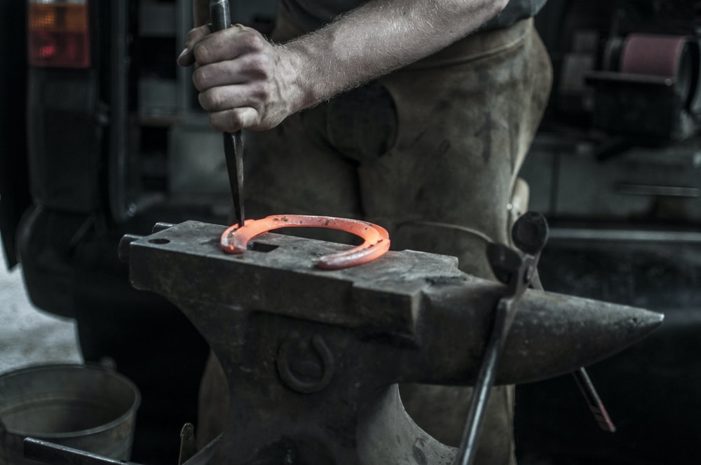 man forging horseshoe