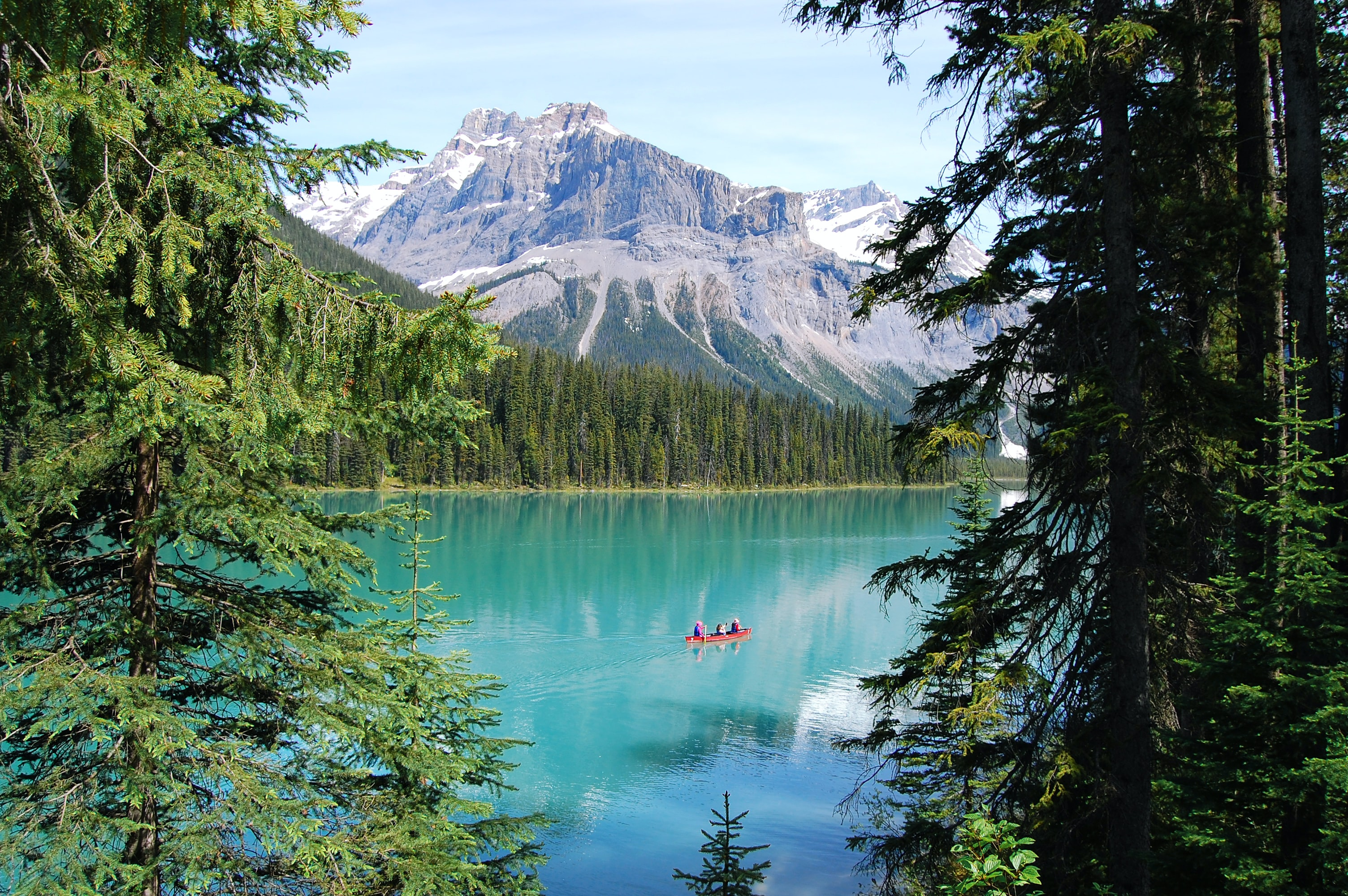 People in a red canoe on Emerald Lake with a tall mountain in the background