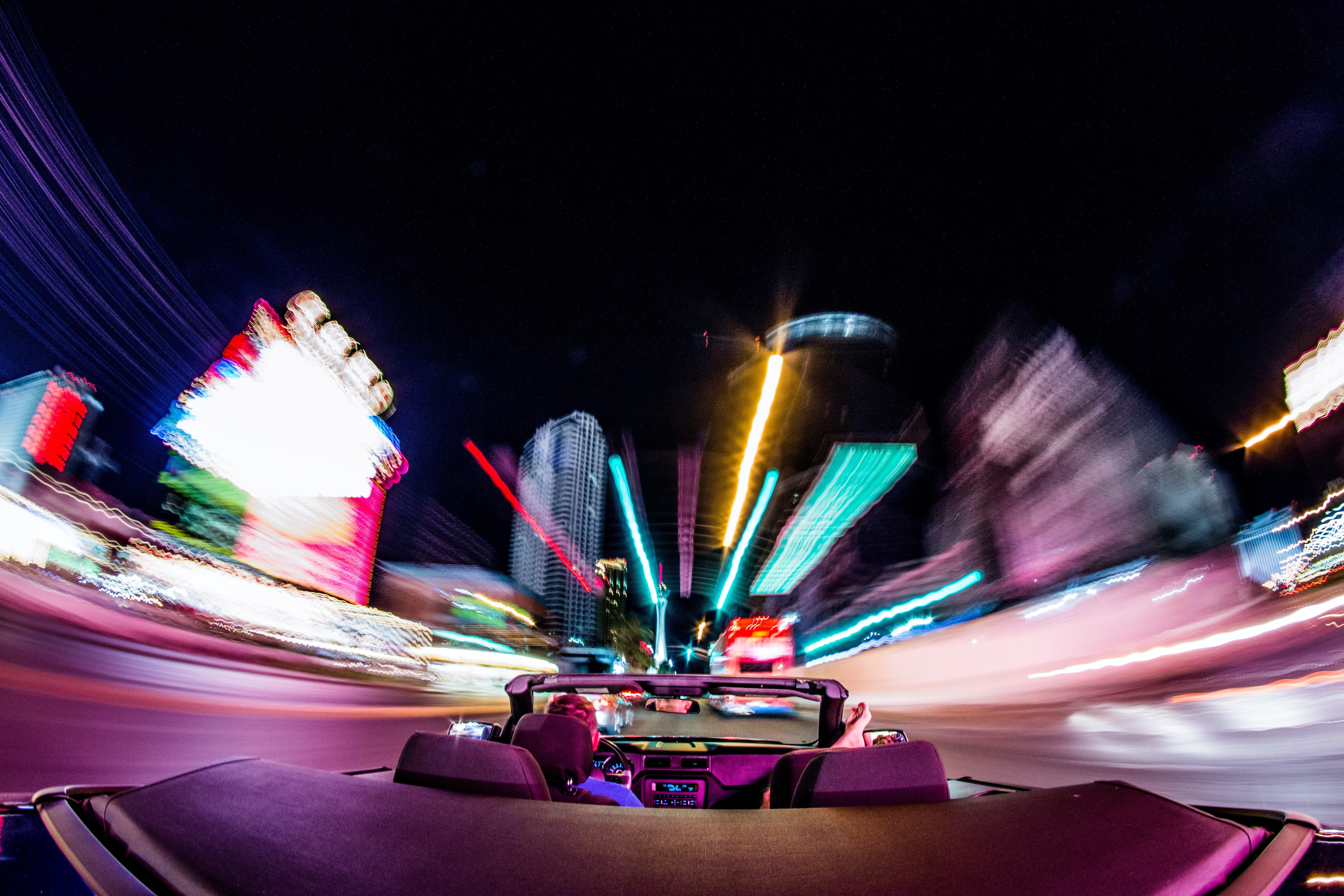 A rear POV of a convertible driving through the Las Vegas strip with light trails.