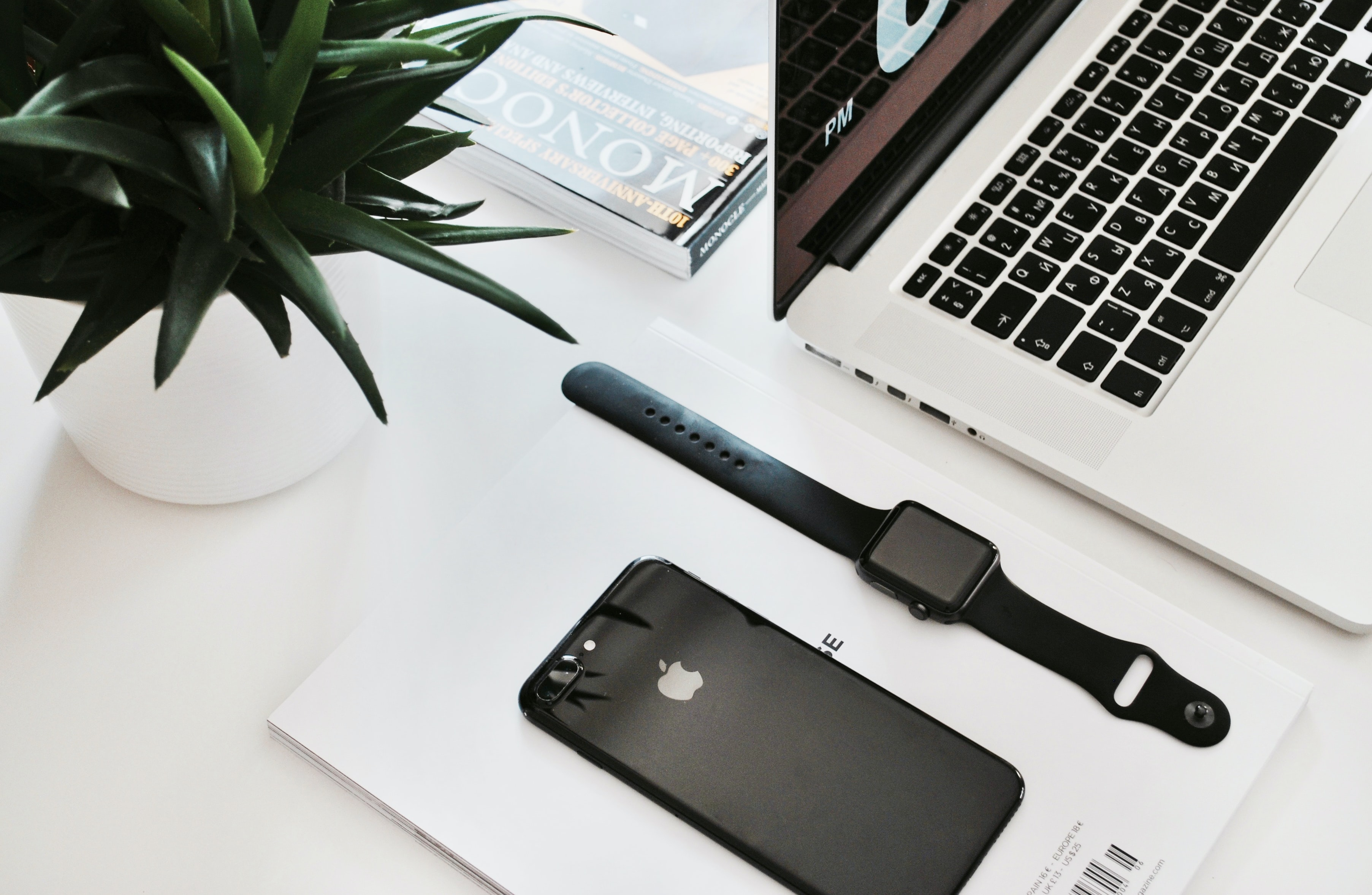 An Apple Watch and an iPhone on a desk next to a laptop