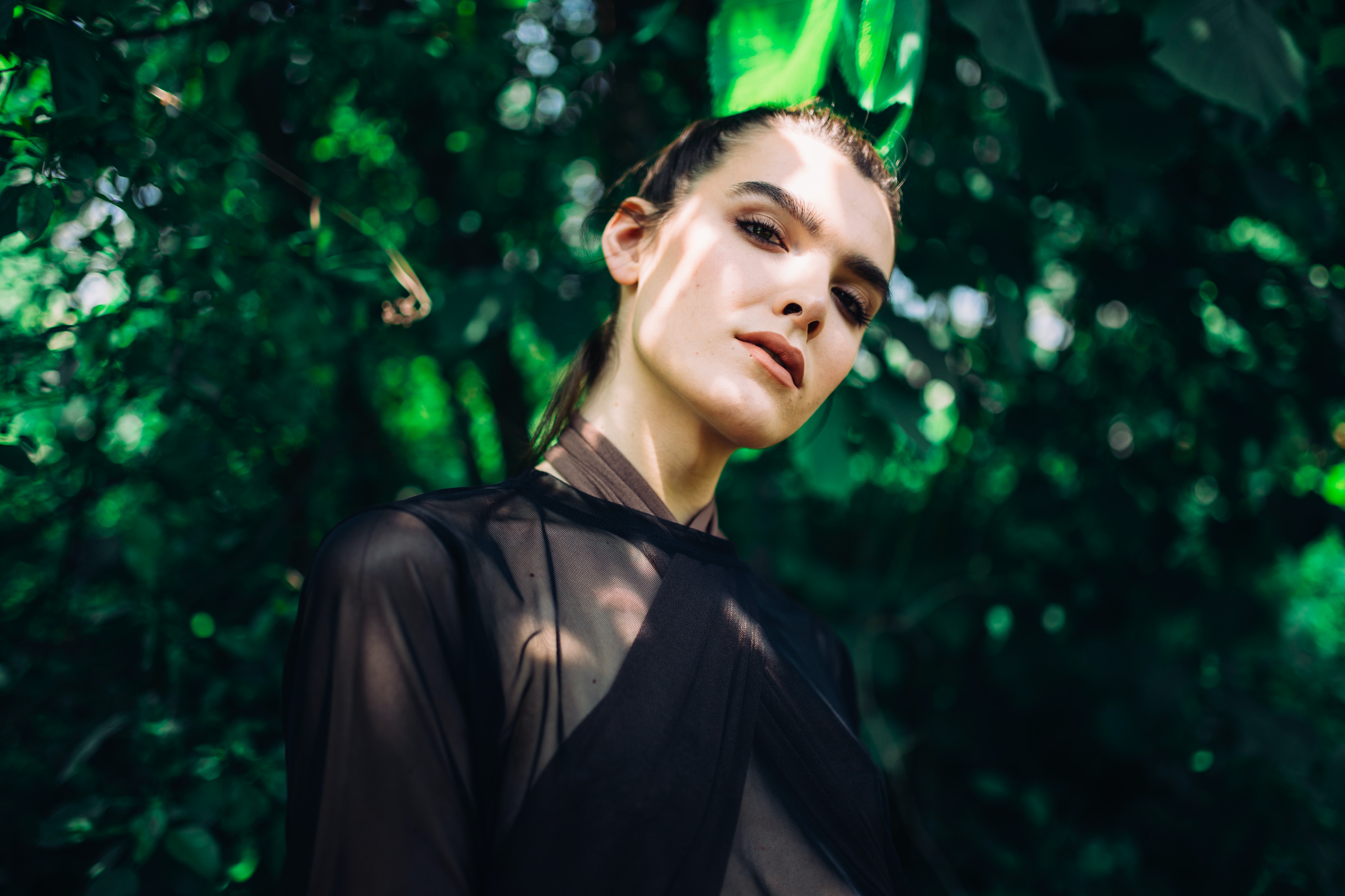 woman wearing sheer top under green leafed plant