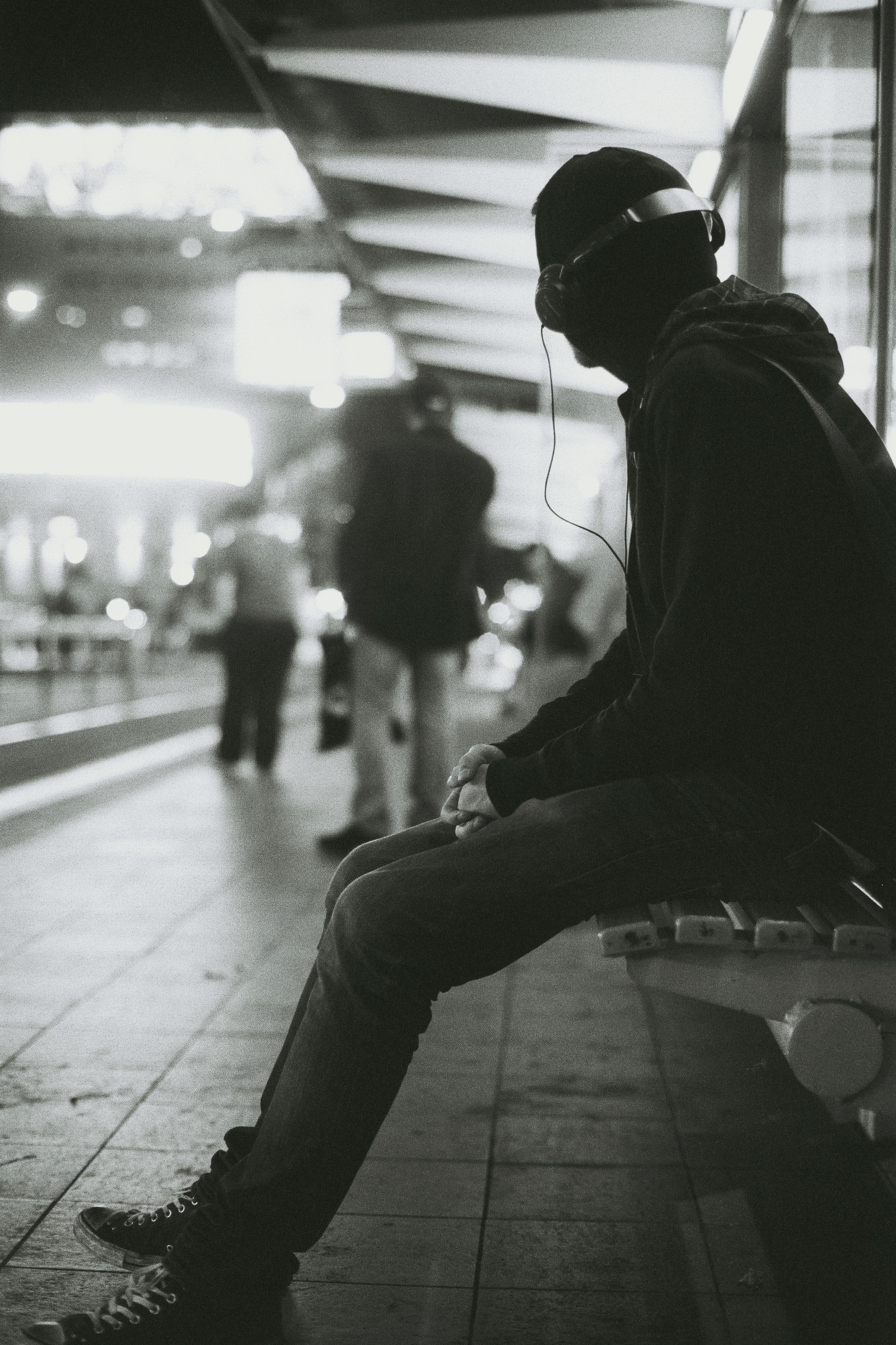 grayscale photography of a man sitting on bench while listening music