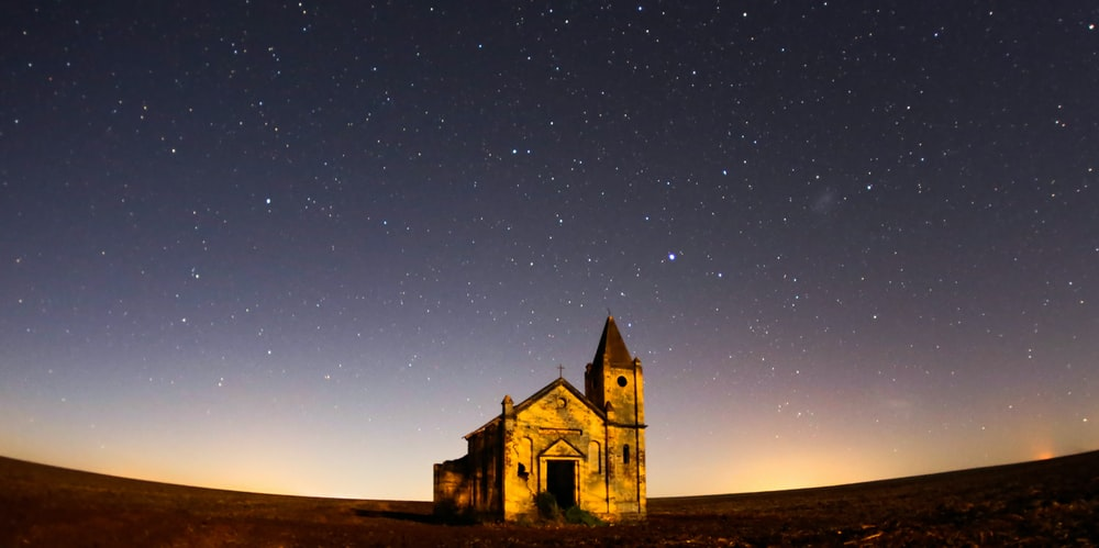 worm's eye view photography of cathedral under gray skies filled of stars