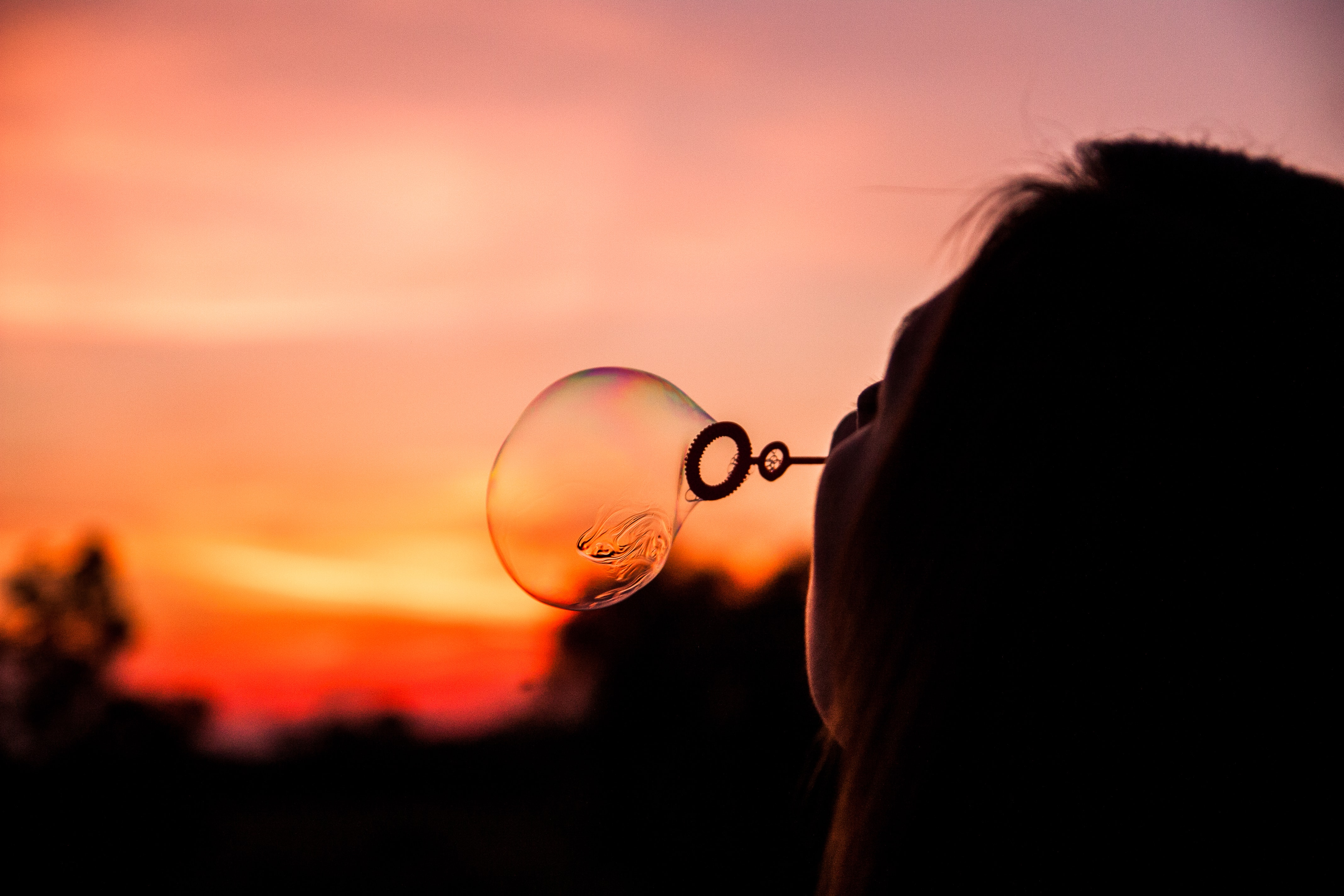 A woman blowing soap bubbles during sunset