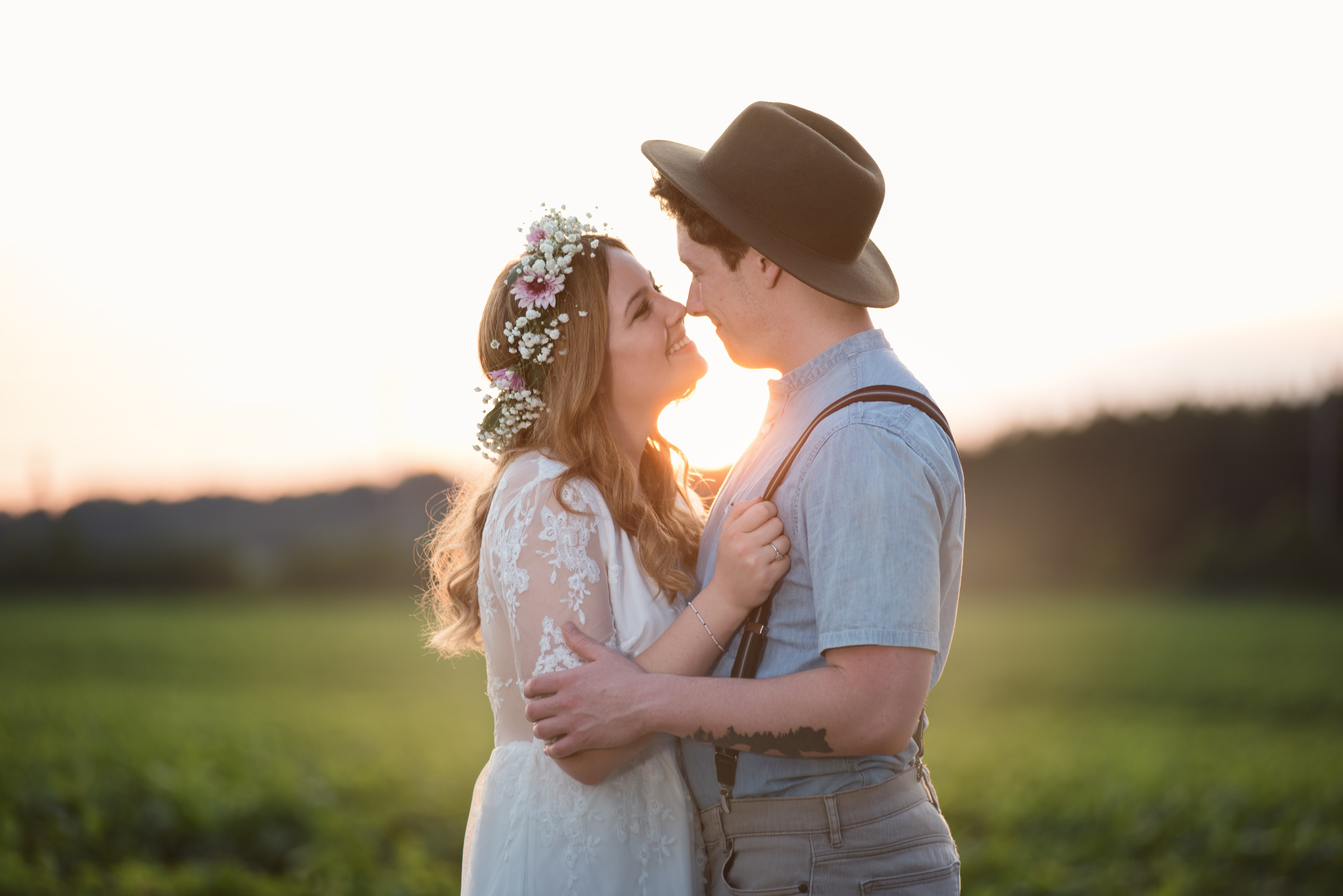 Bride with flower crown and groom with hat smile at each other at sunset