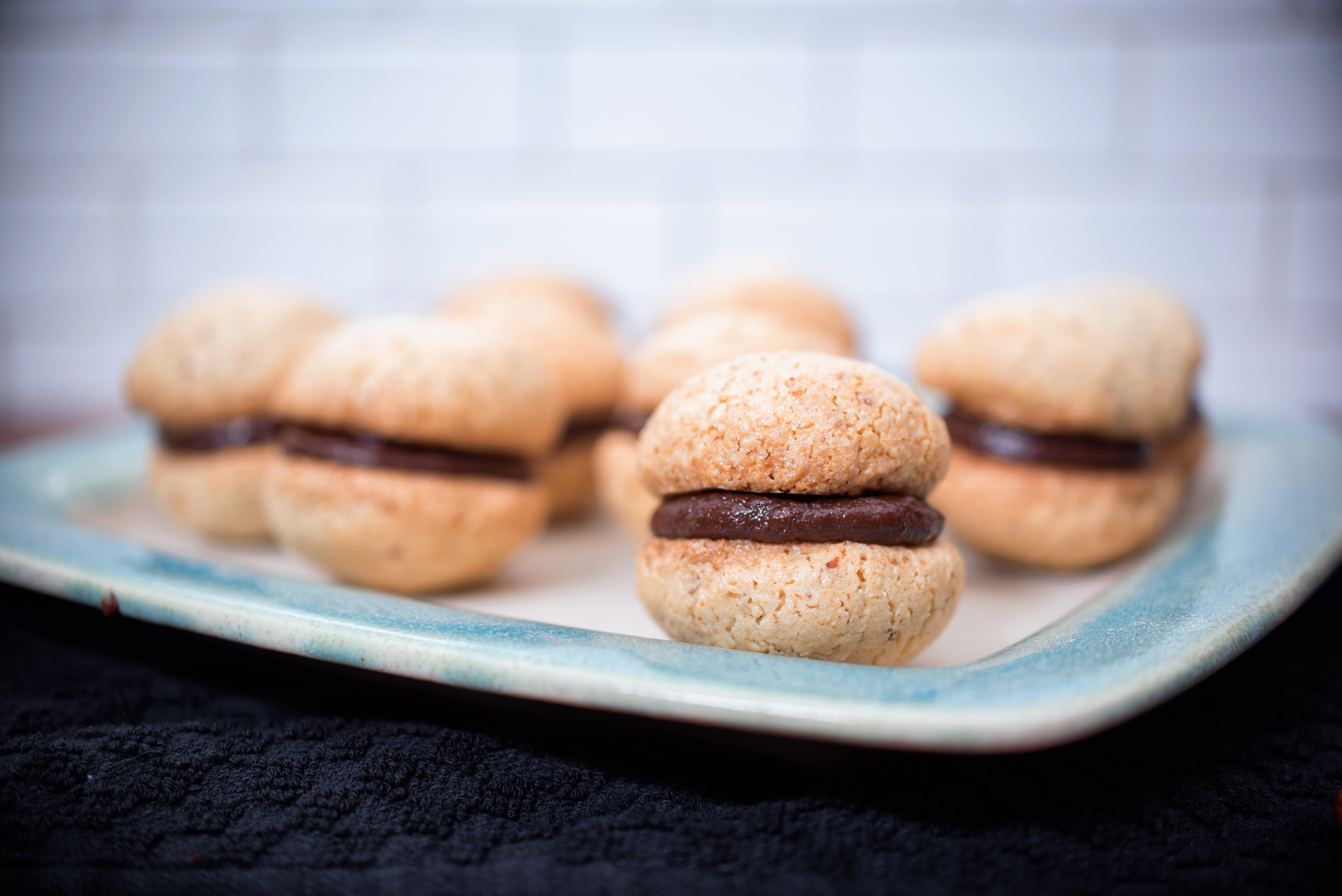 Small plate of chocolate fresh macaron pastries