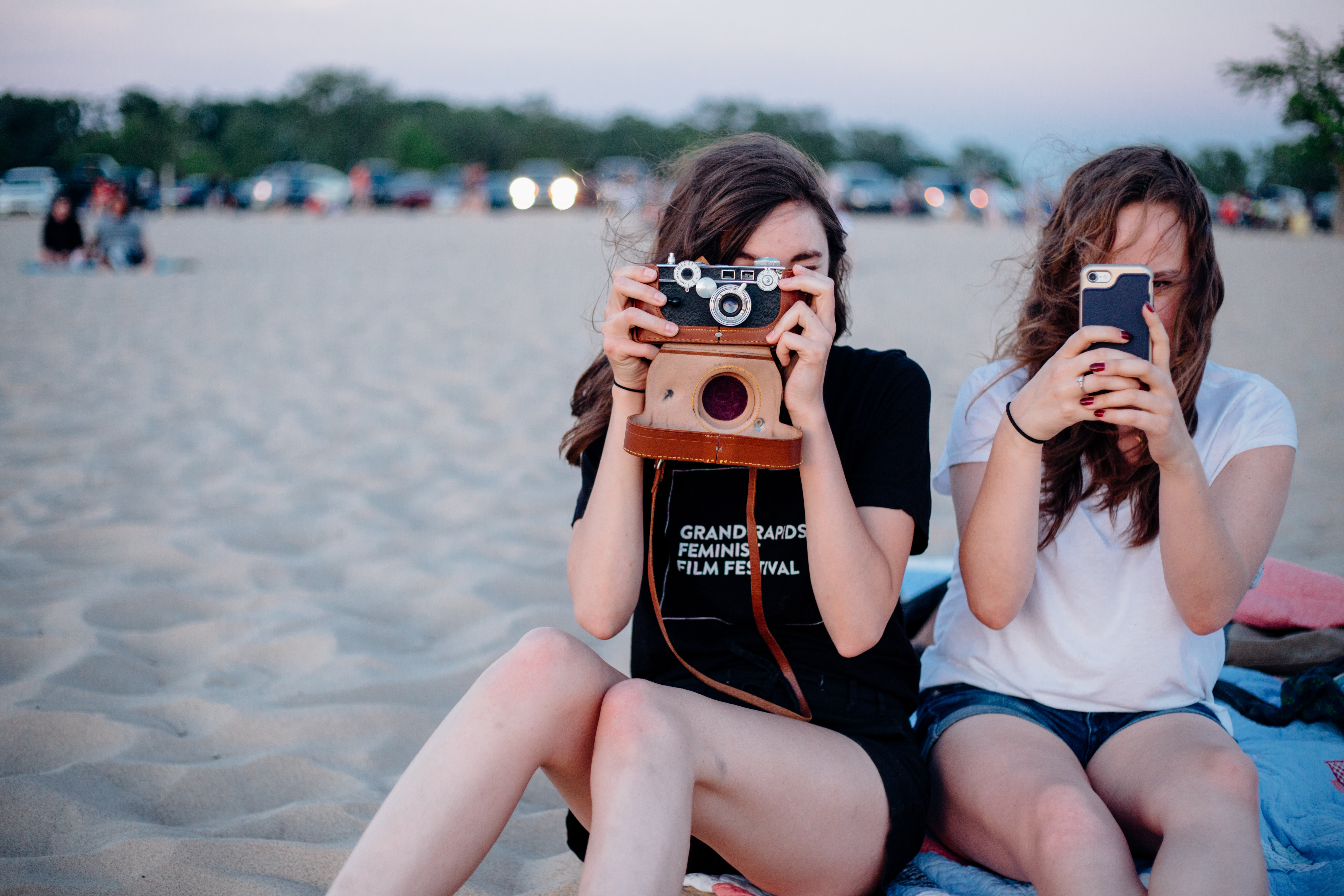 Two female friends are taking photos with a vintage camera and a smartphone at the beach.